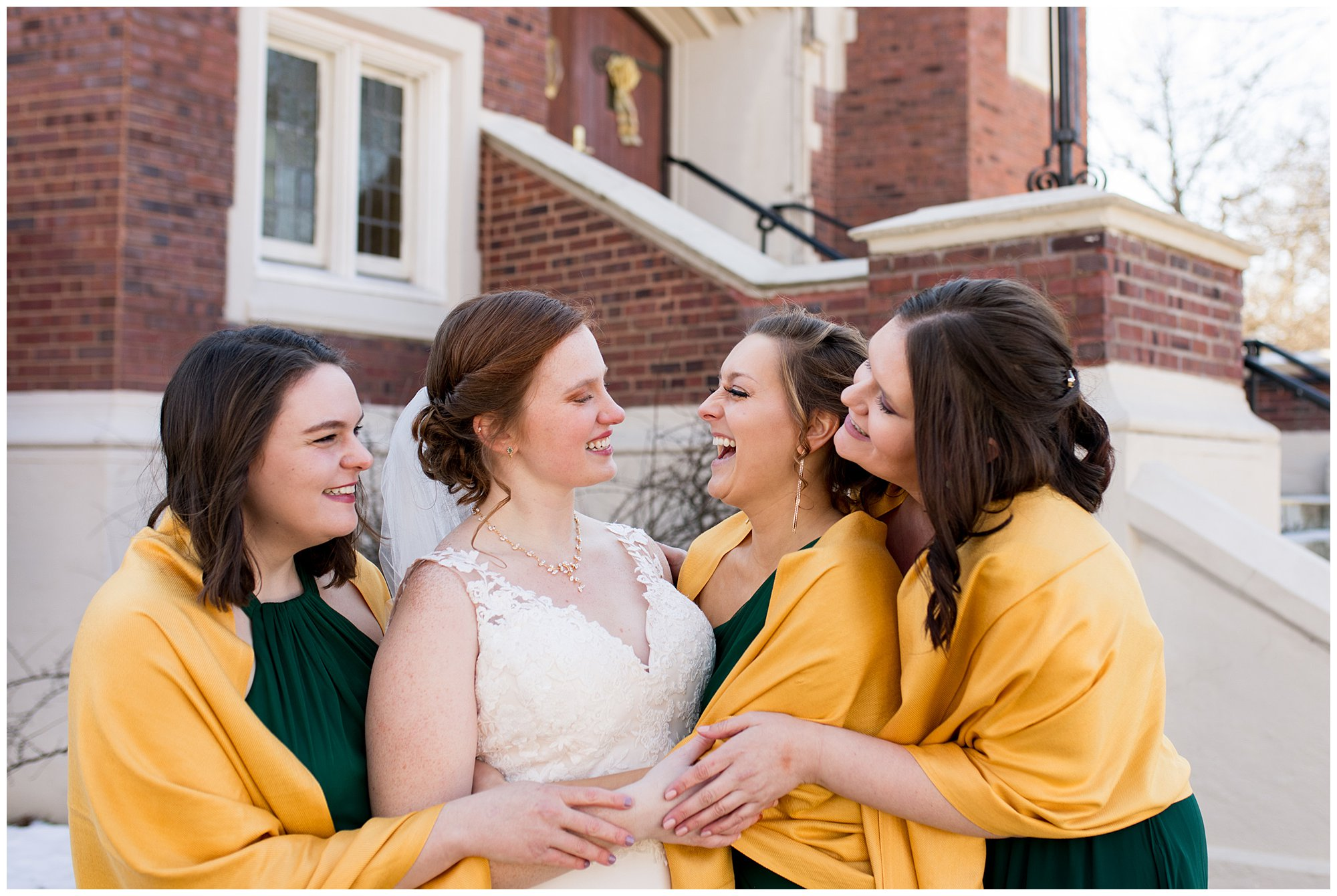 bride and bridesmaids laugh together outside of church before wedding ceremony