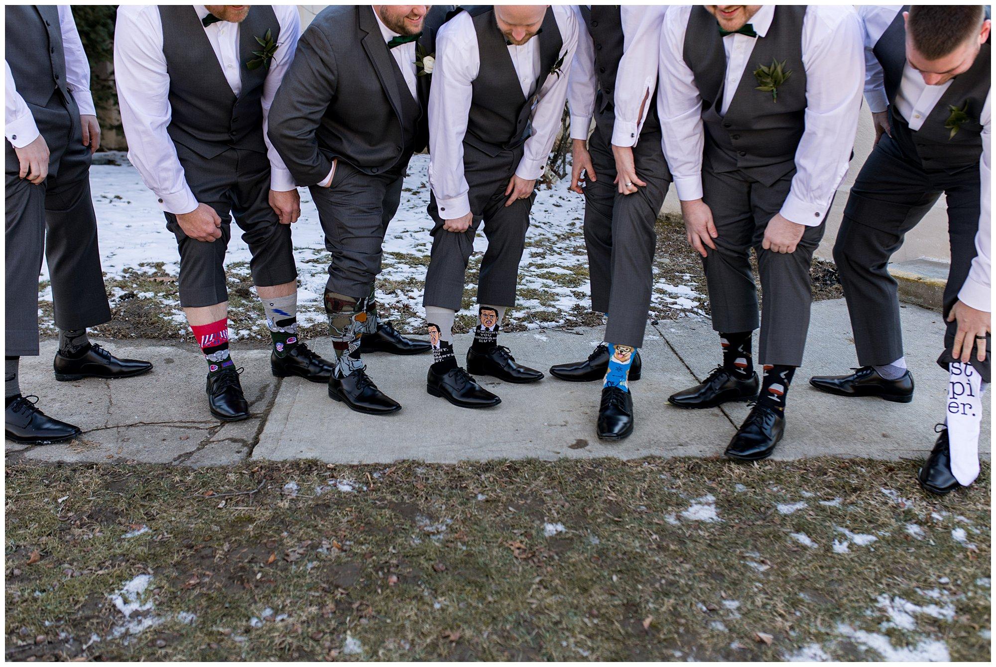 groom and groomsmen show off fun socks