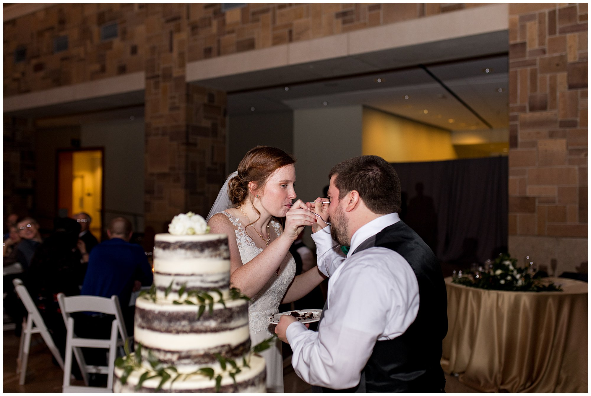 bride and groom feed each other wedding cake from Kahn's Catering