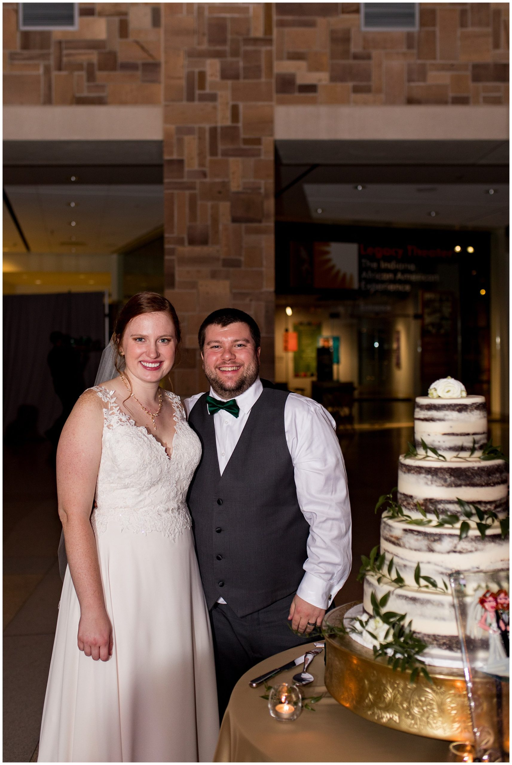 bride and groom stand beside wedding cake from Kahn's Catering