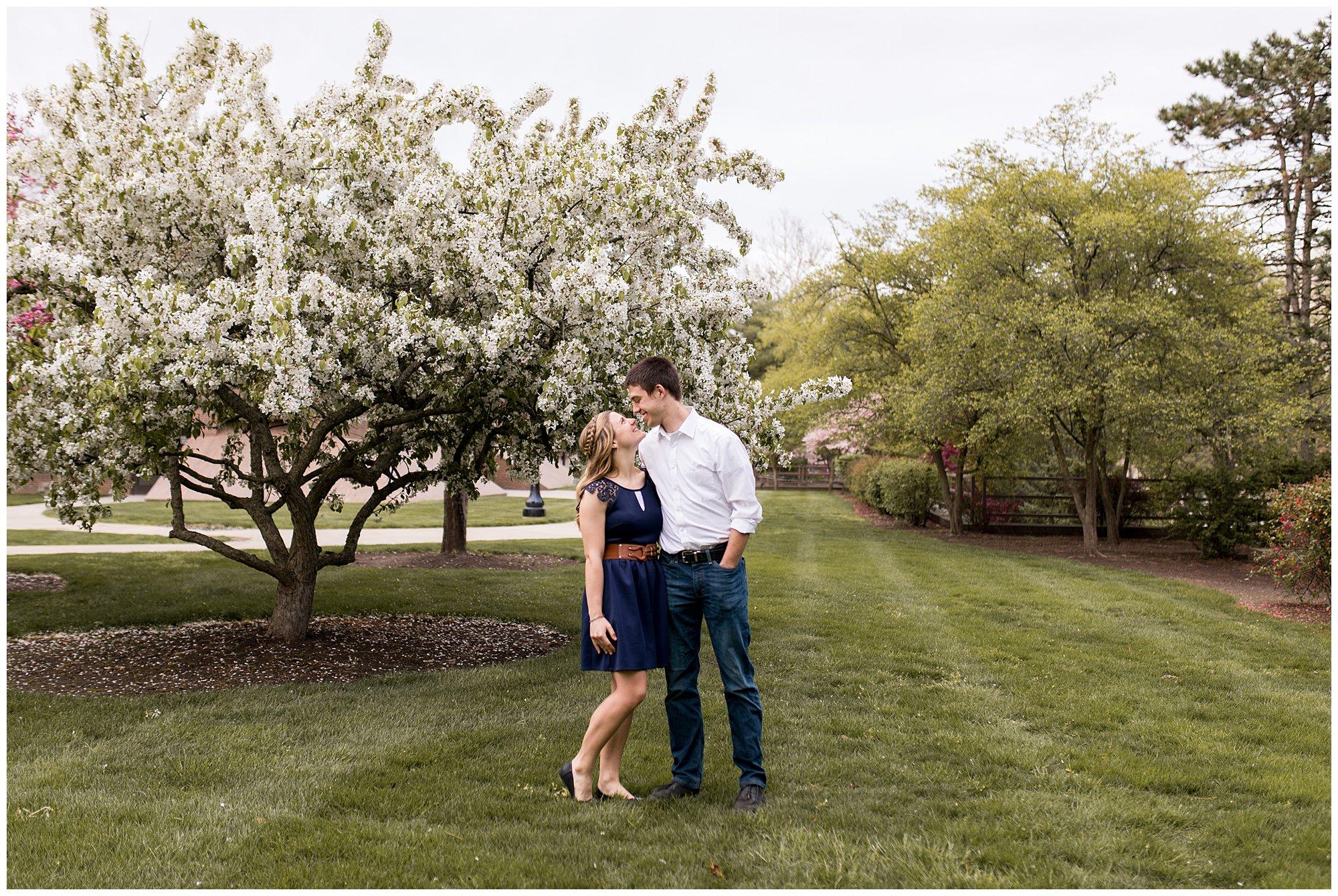 couple looking at each other during engagement photos in front of flowering tree at Purdue University