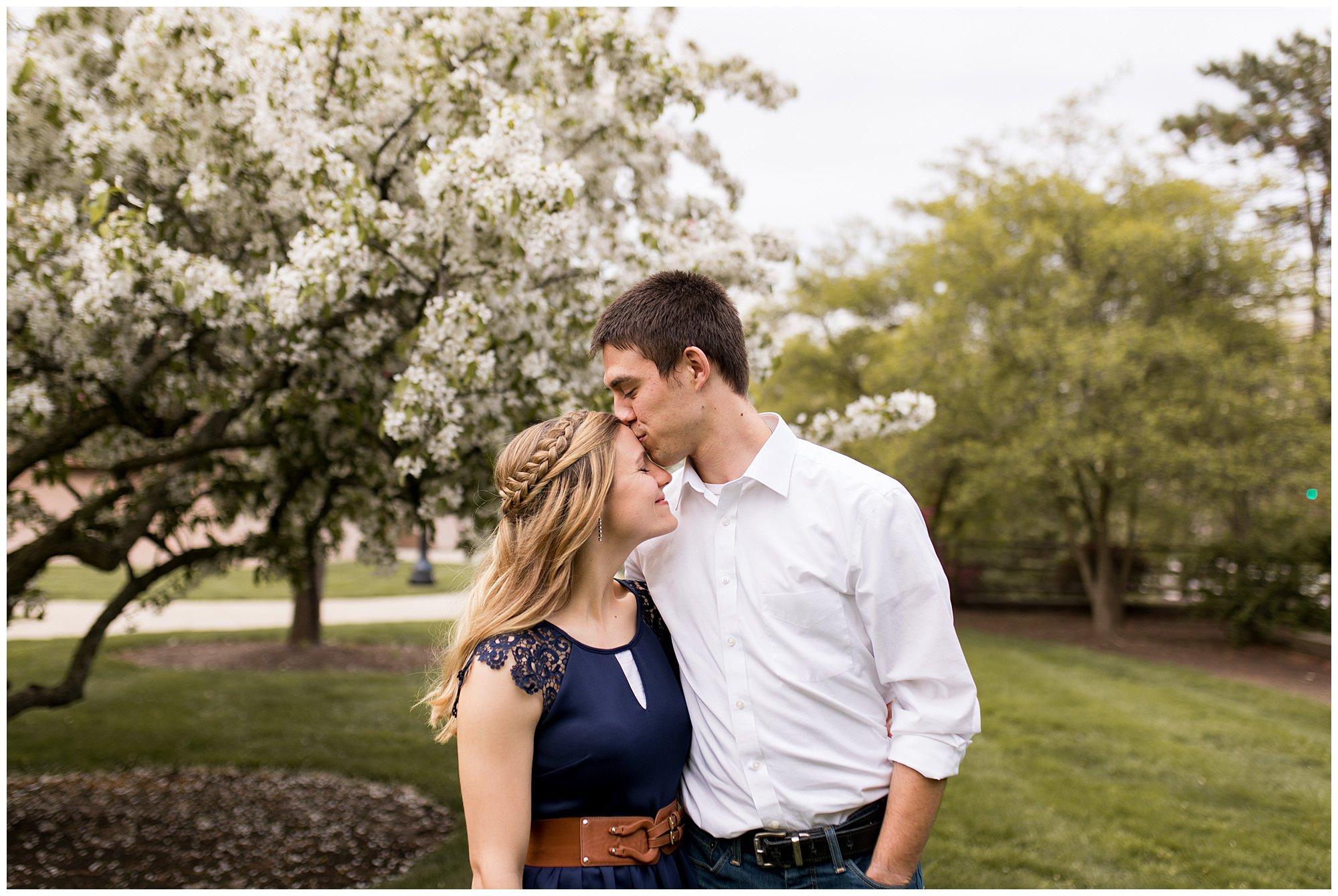 groom kisses bride's head during engagement photos at Purdue University