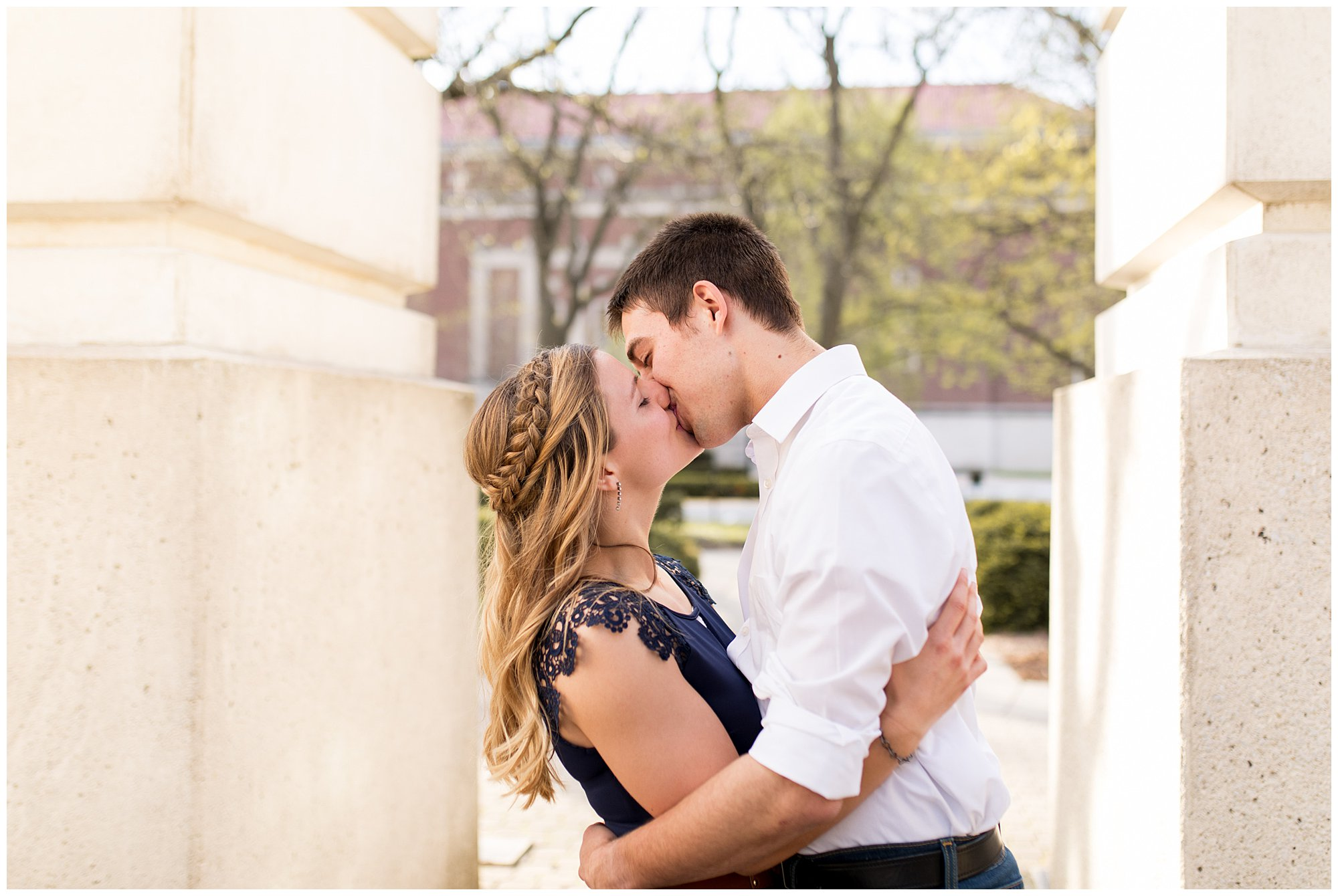 bride and groom kiss under clock tower at Purdue University