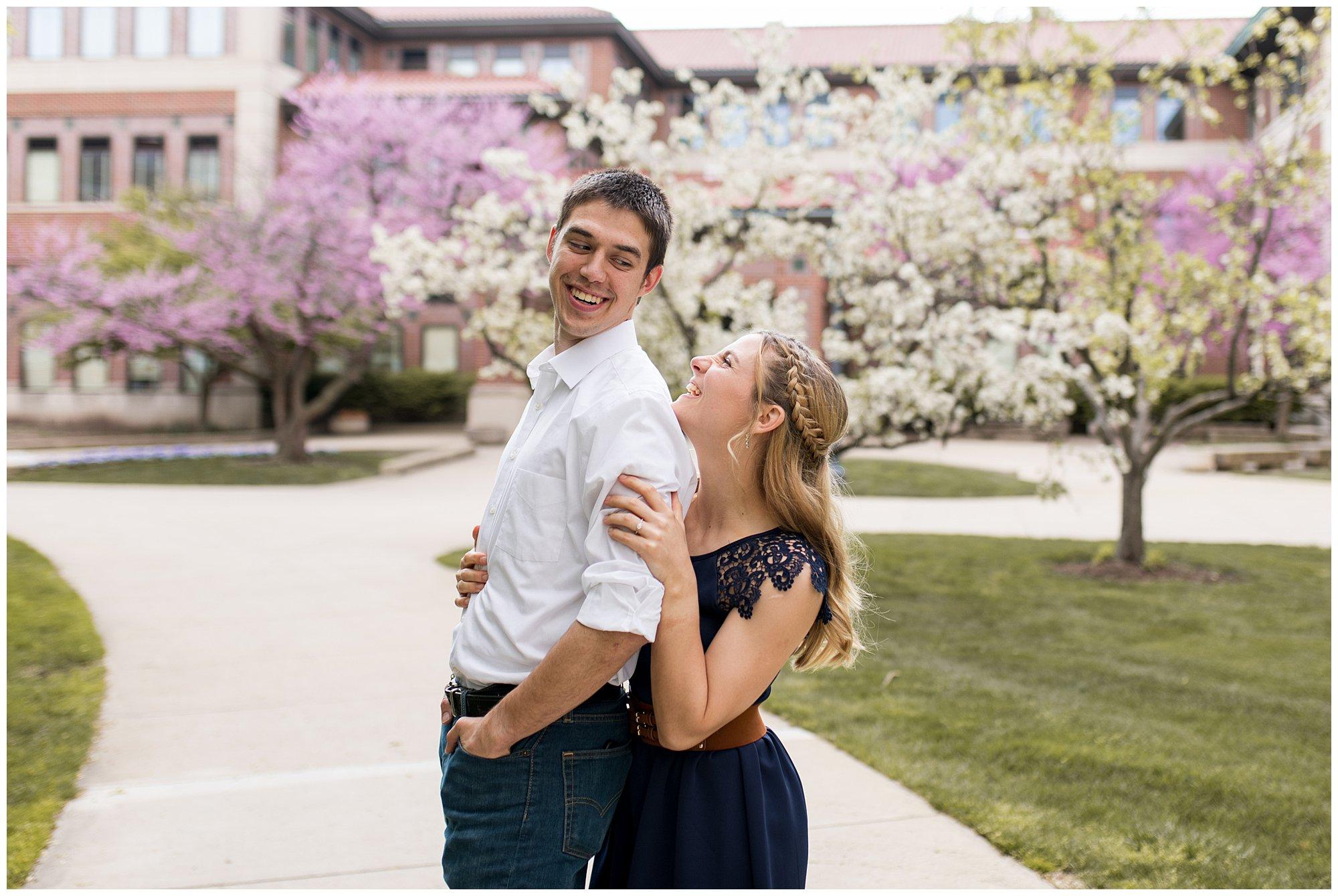 groom looks over shoulder at bride during engagement session on campus