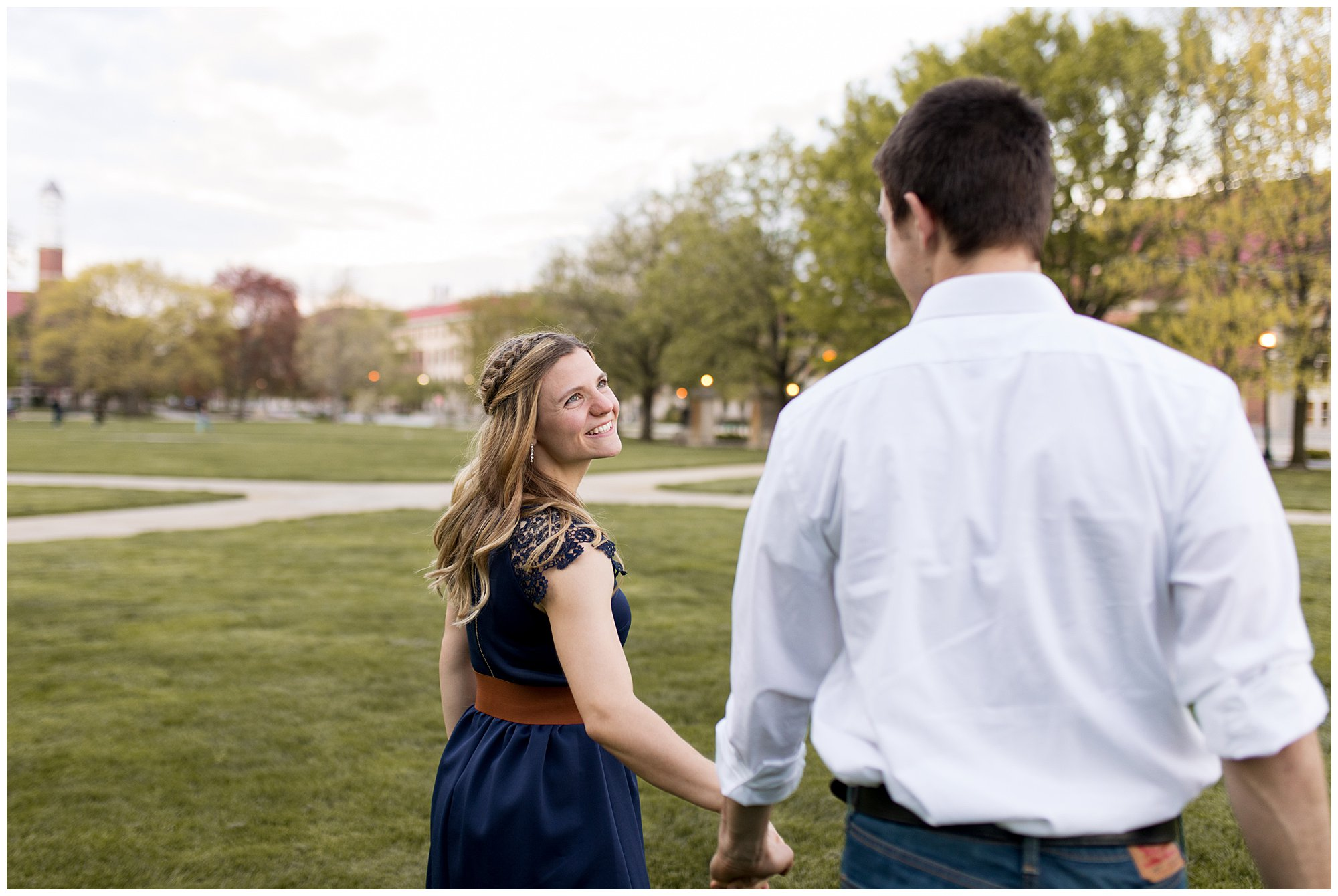 couple holds hands and walks through Purdue University