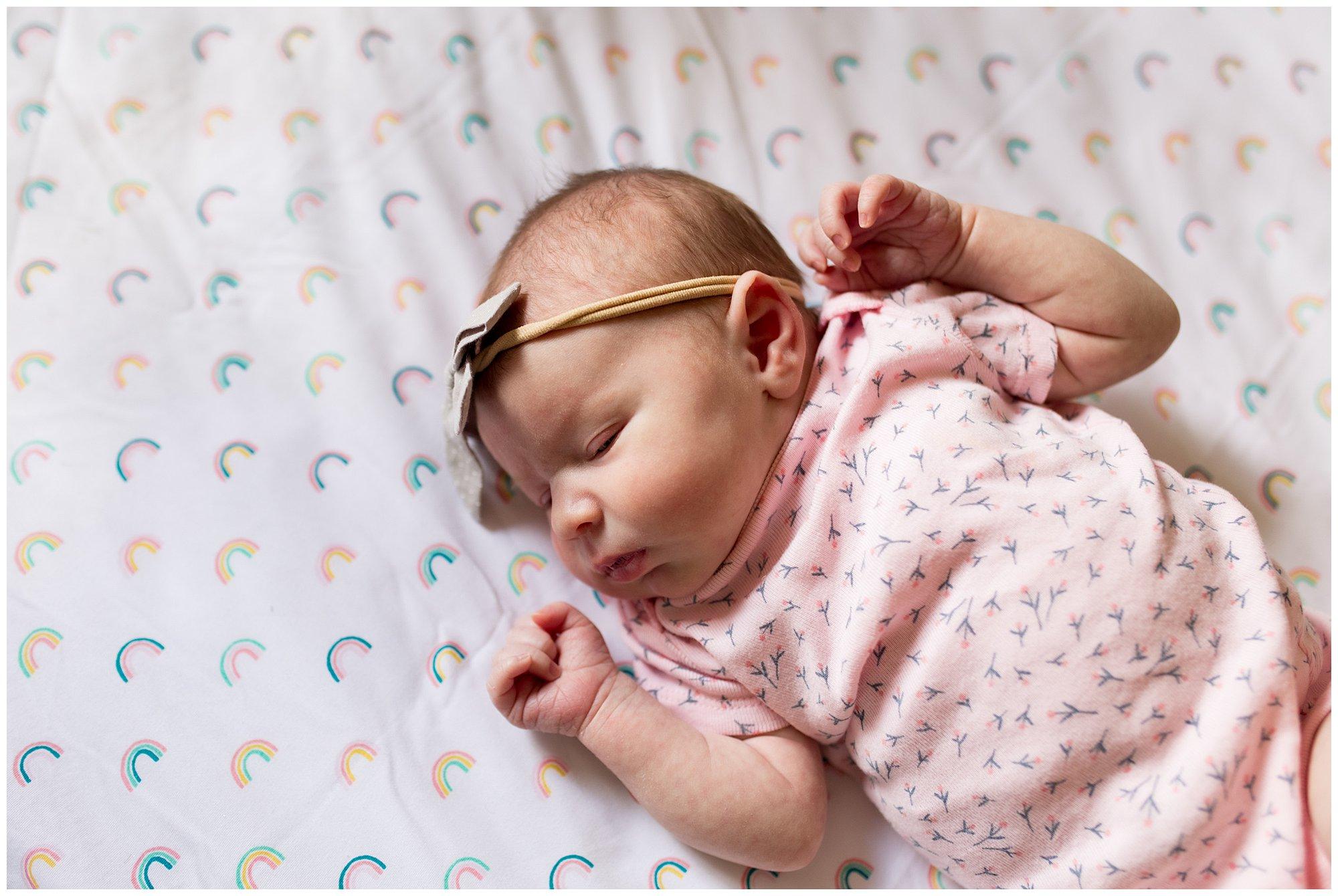 newborn baby sleeping on rainbow crib sheets with bow around head