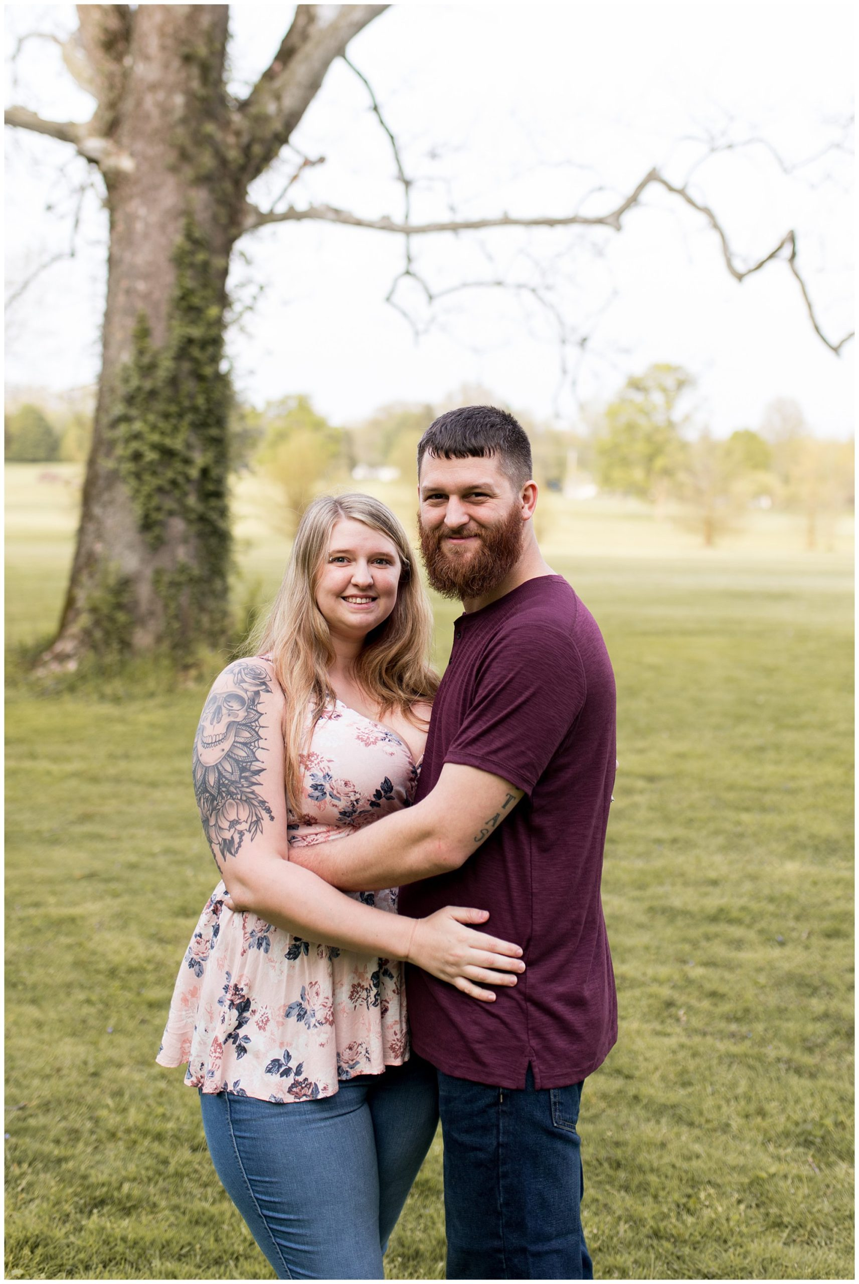 engaged couple smiles at camera during engagement session at Foster Park in Fort Wayne Indiana