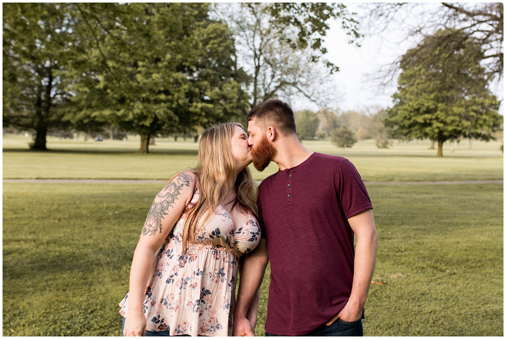 couple holds hands and kisses during engagement session at Foster Park in Fort Wayne