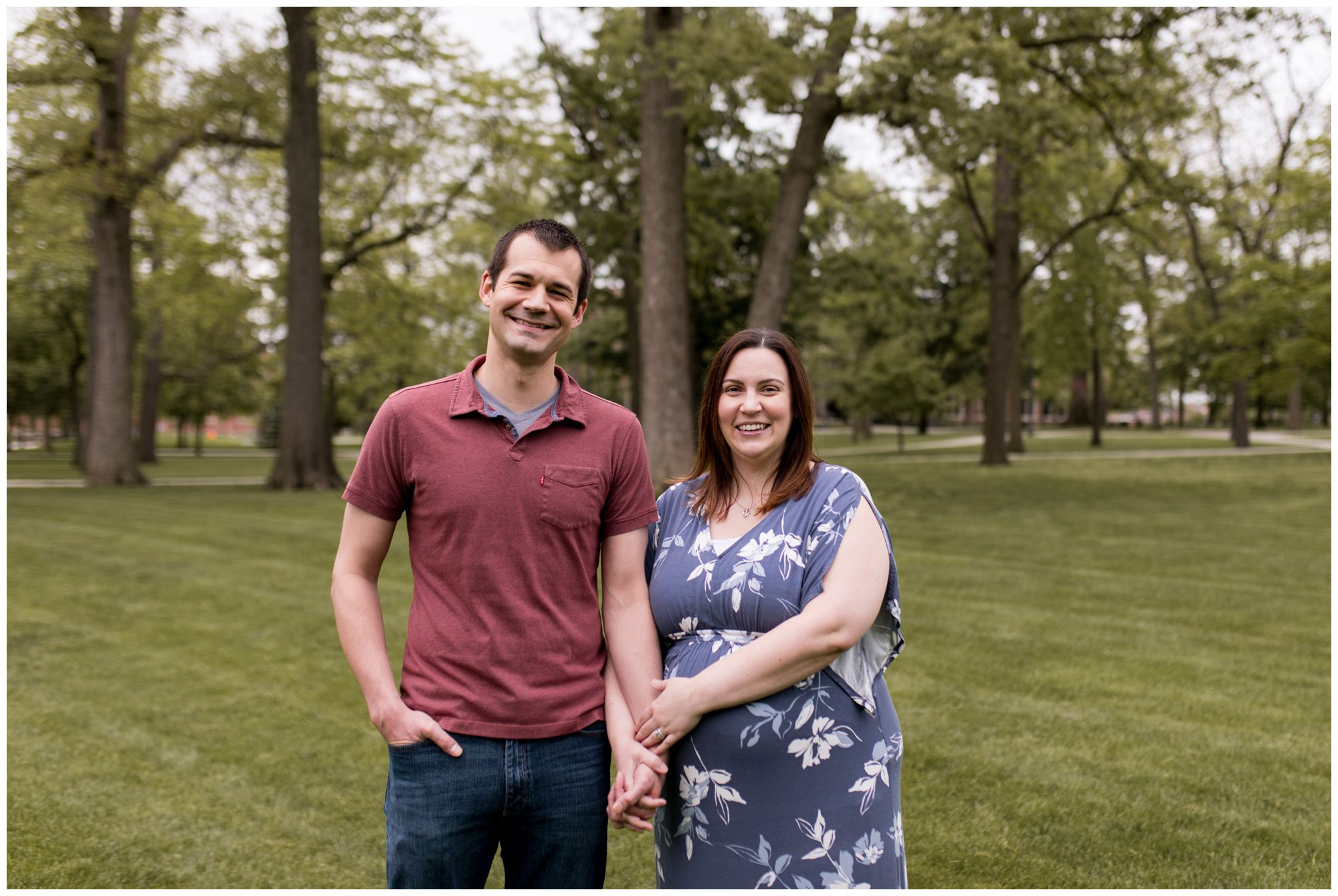 mom and dad hold hands during maternity session at Ball State University