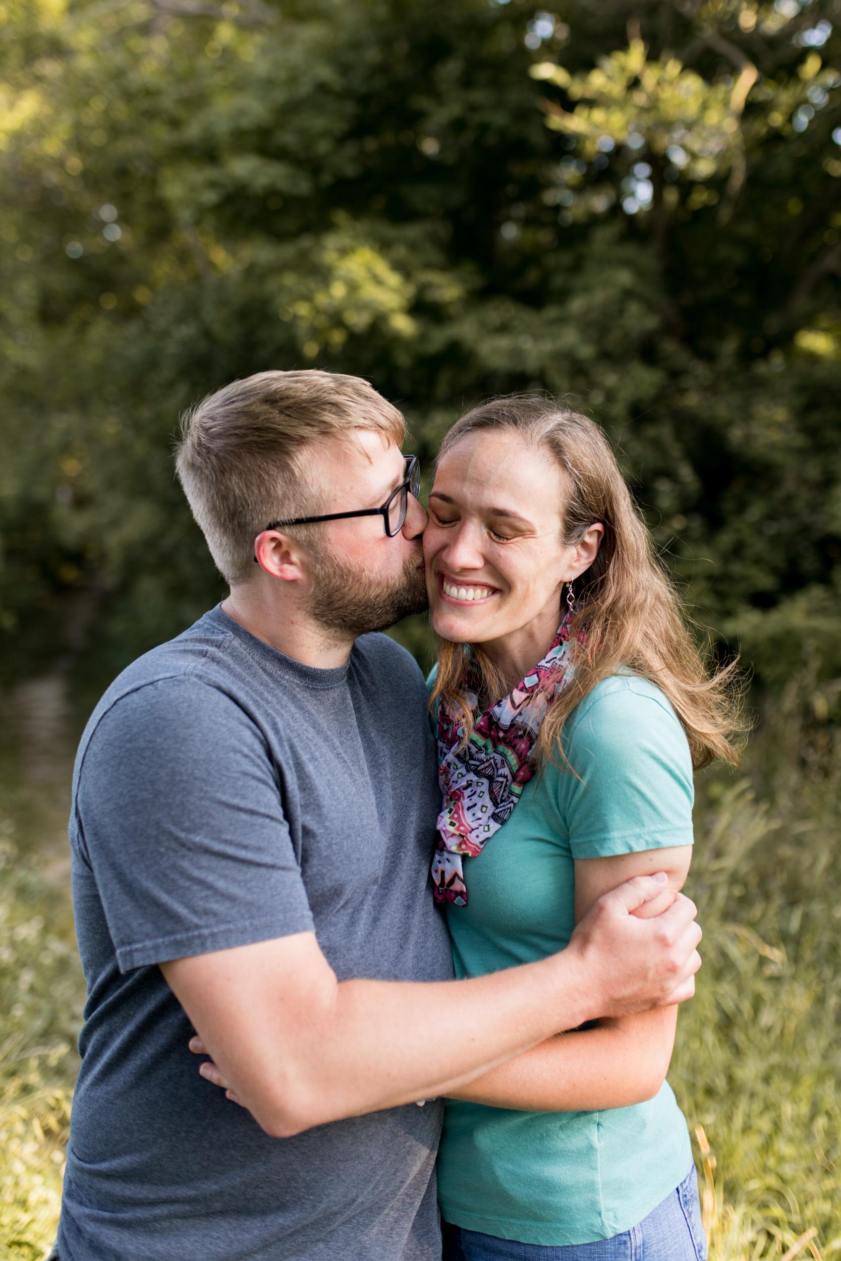 dad kisses mom on cheek during family session at Kokomo Reservoir