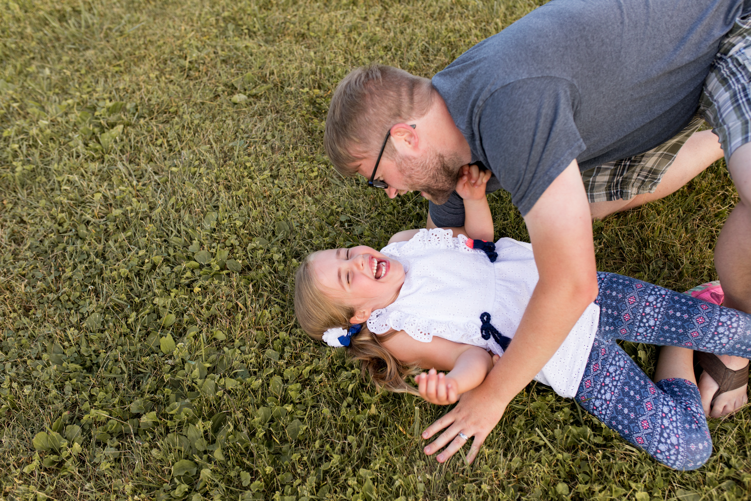 dad laughs with daughter in grass