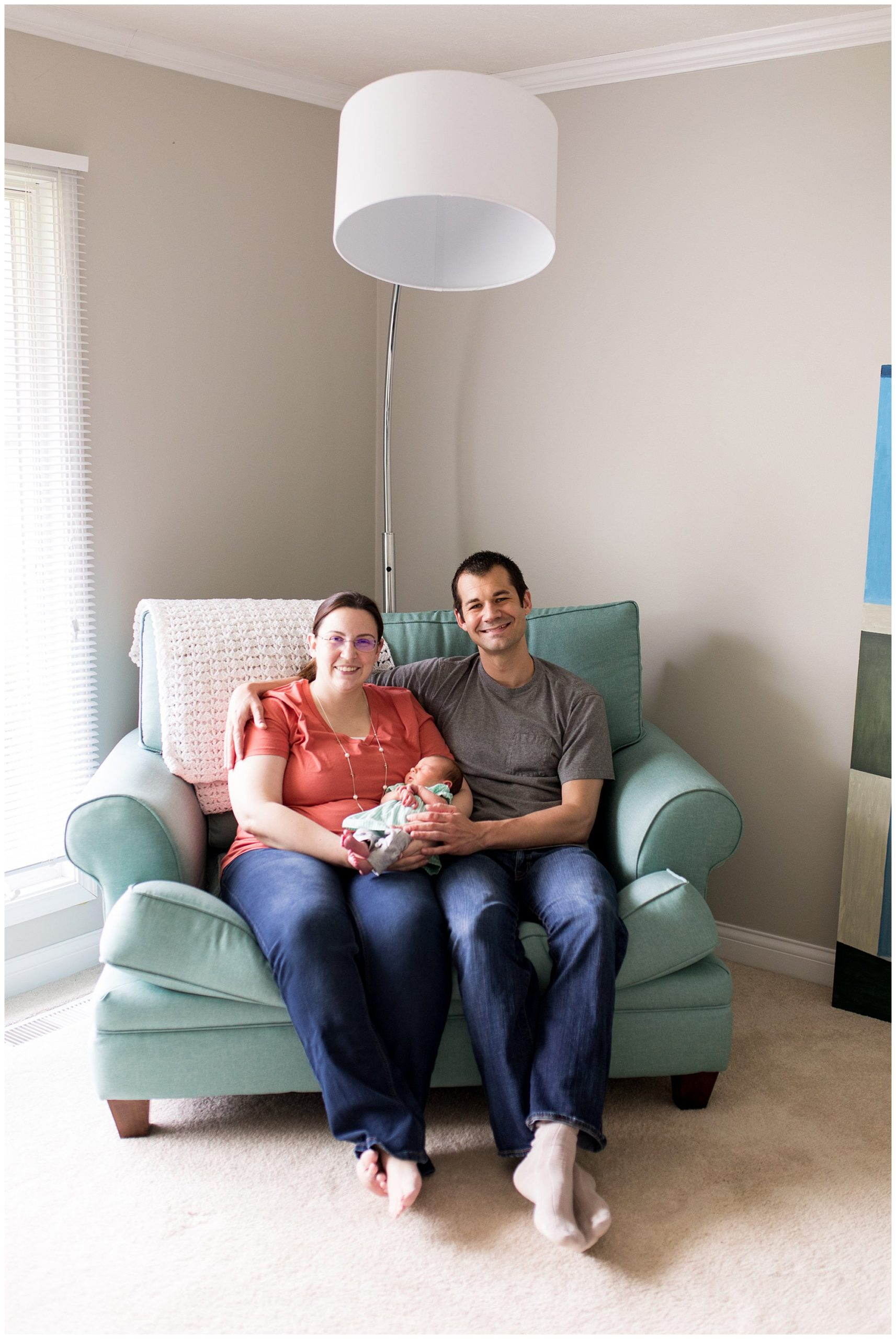 mom and dad hold baby in living room during Muncie newborn session