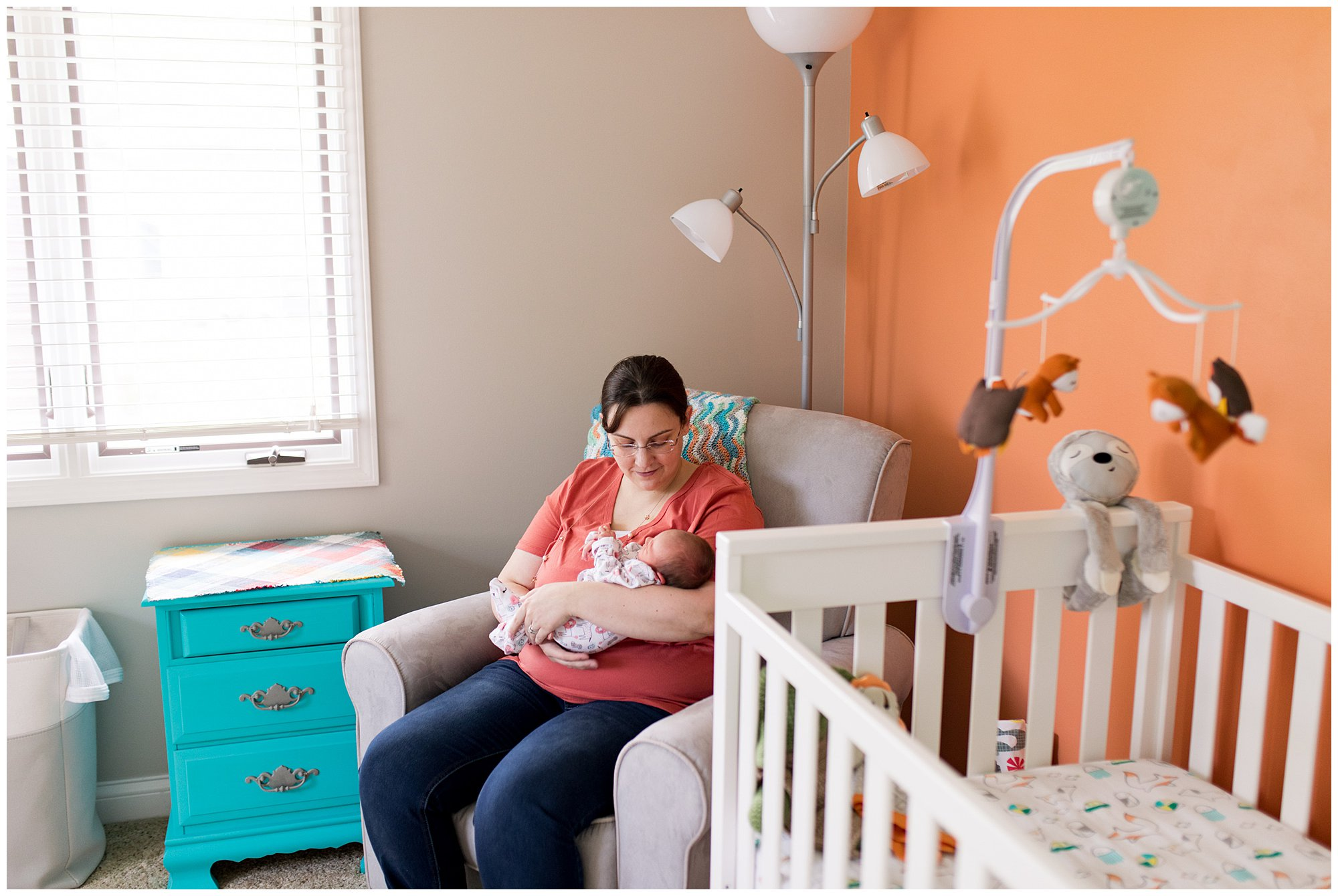 mom holds newborn in nursery during in-home newborn session