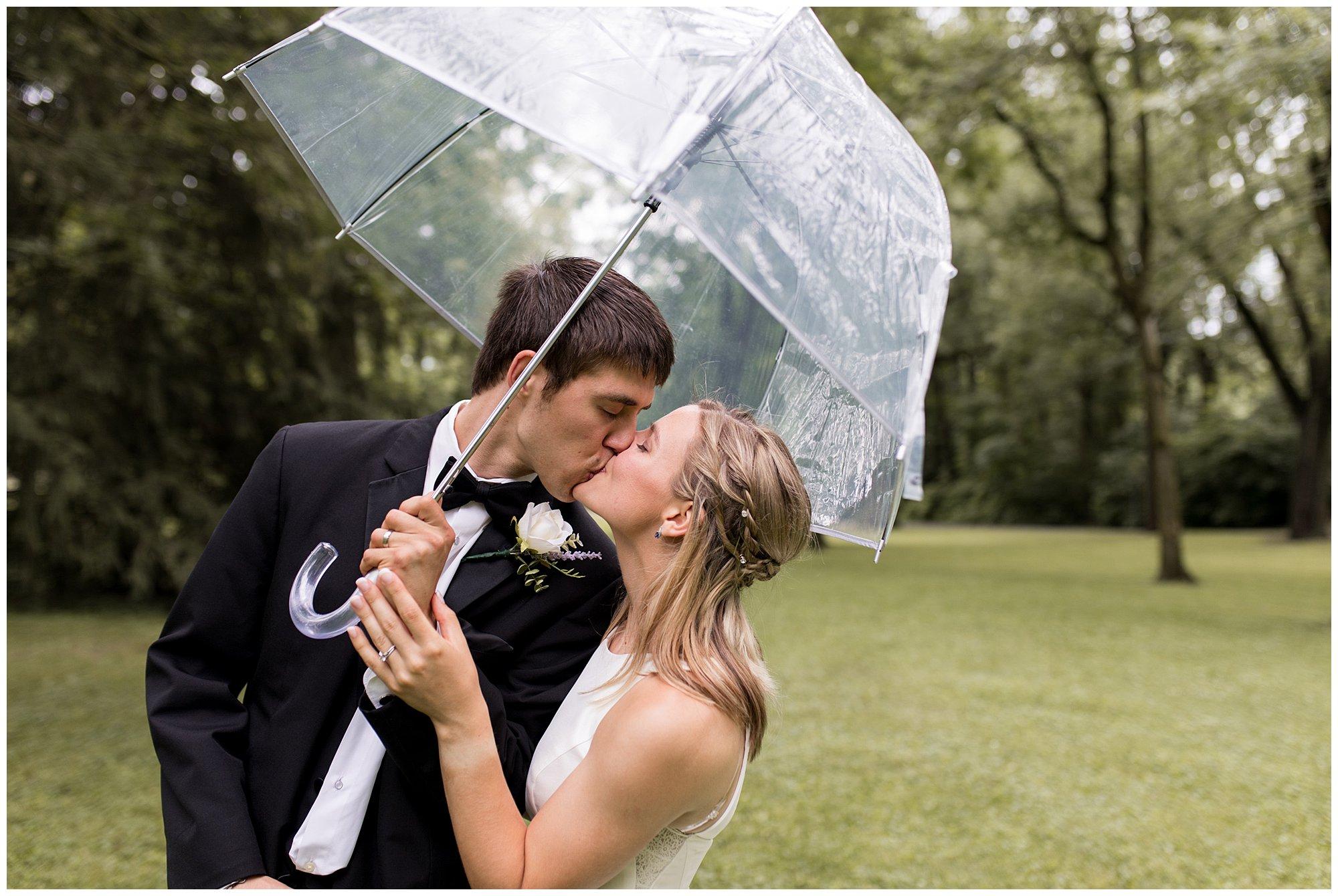 bride and groom kiss under umbrella at Highland Park in Kokomo Indiana