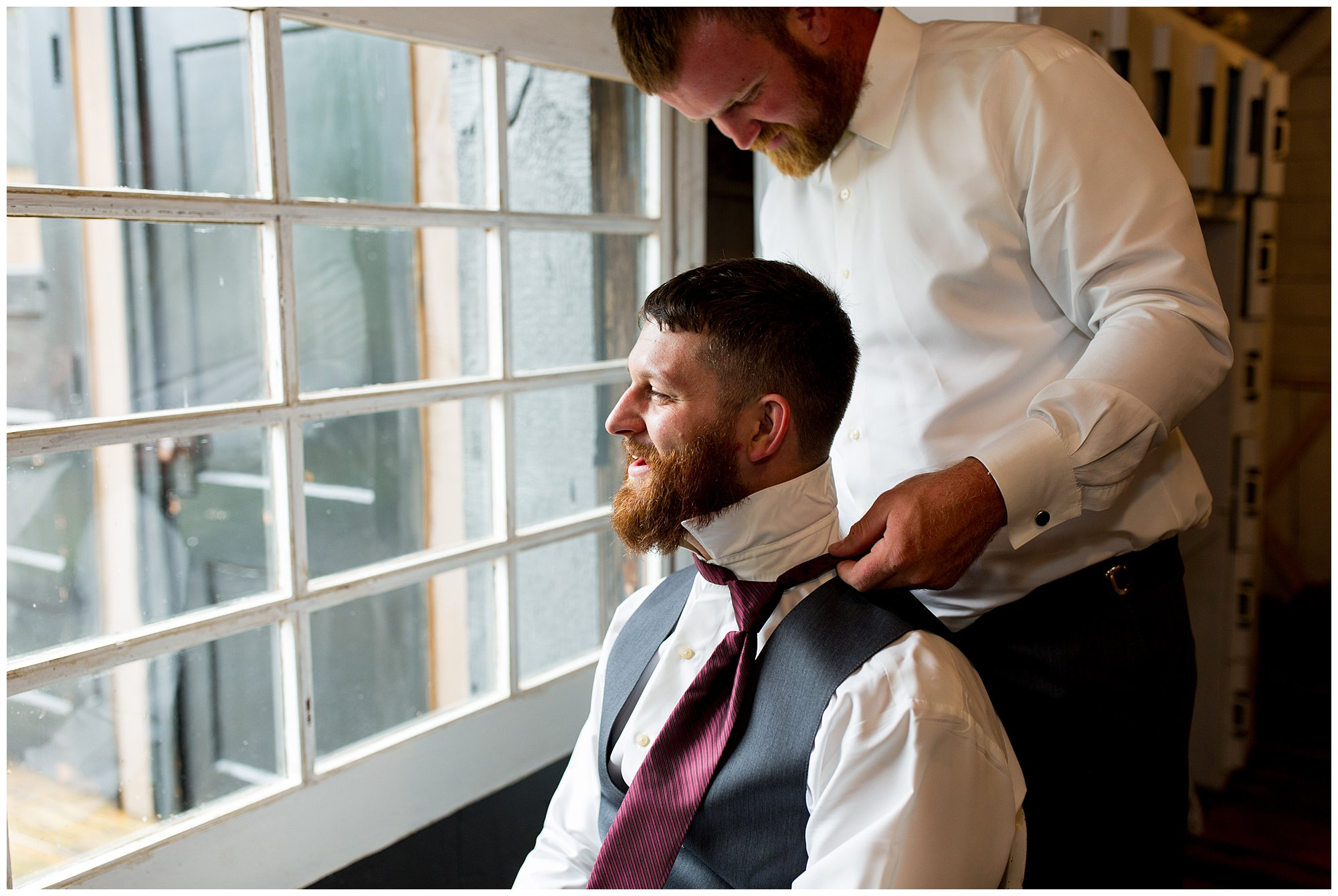 groom getting tie put on before wedding ceremony in Fremont, Indiana