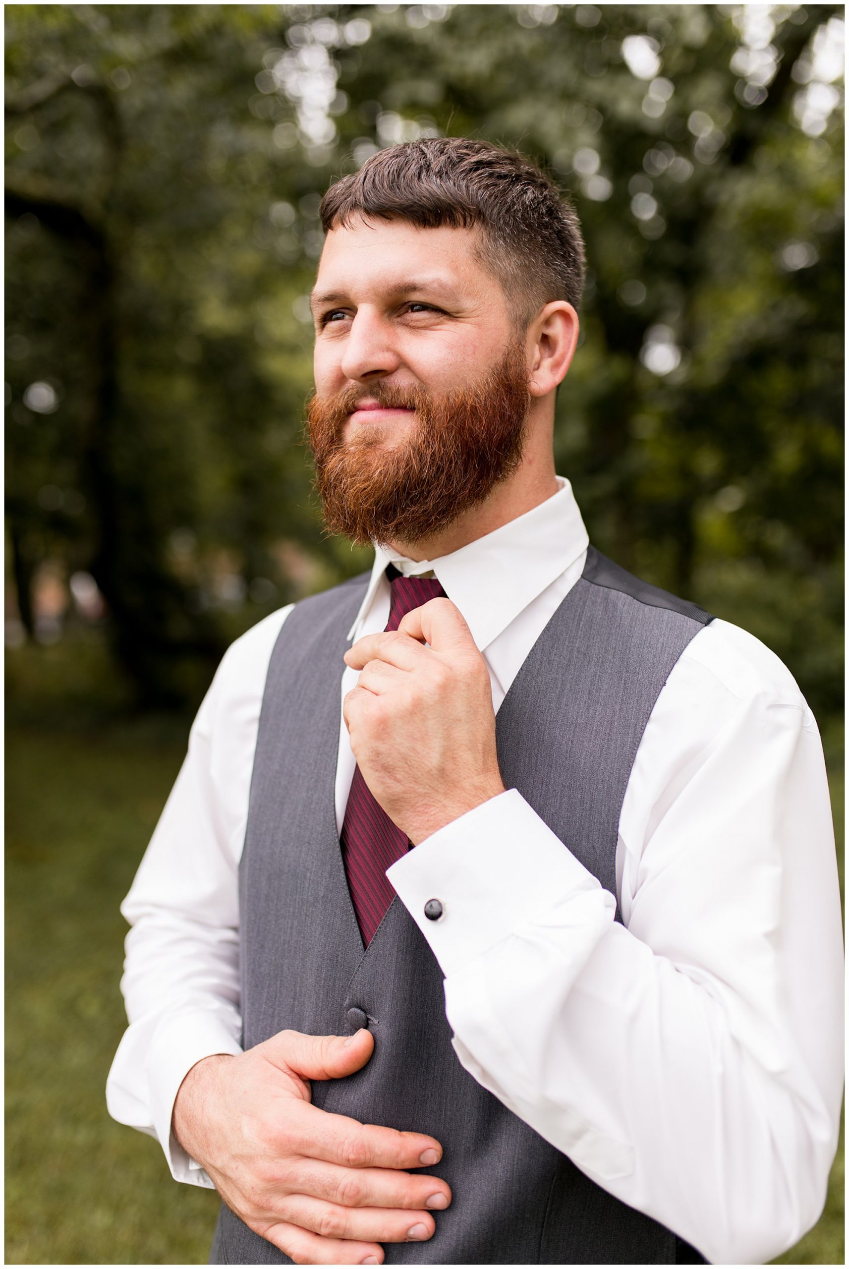 groom straightening tie at The Old Mill Village wedding in Fremont Indiana