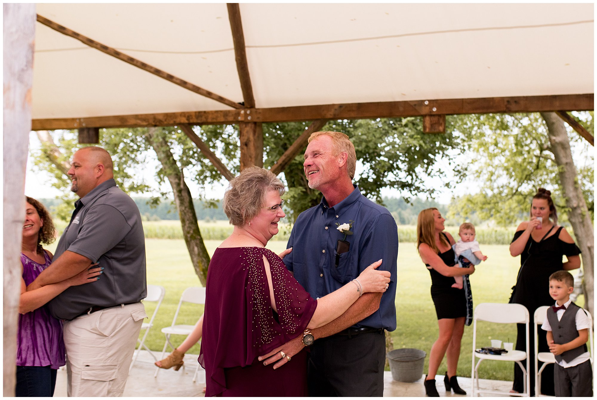 groom's mom and dad dance during reception at The Old Mill Village