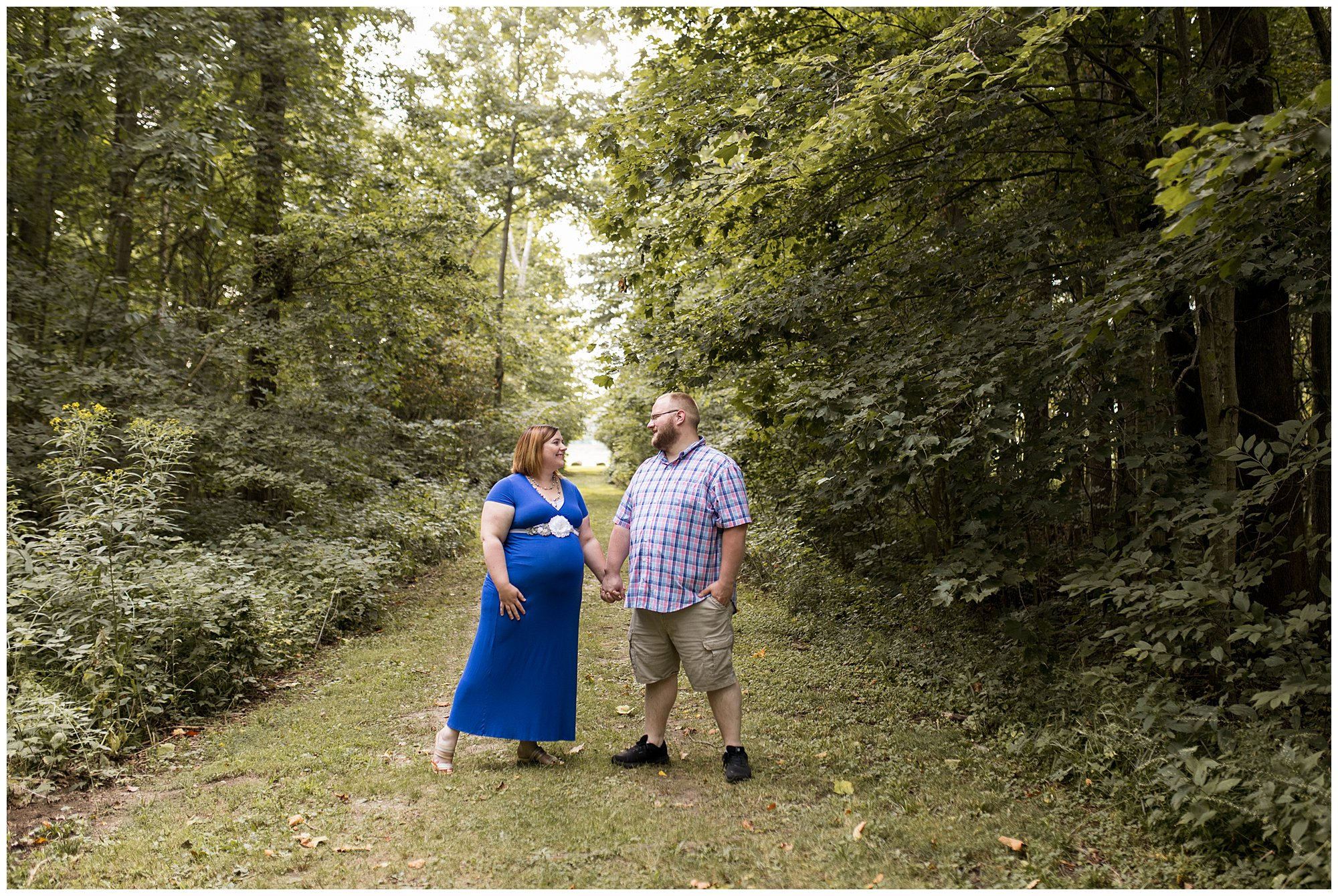 mom and dad hold hands during maternity session at Jackson Morrow Park in Kokomo Indiana