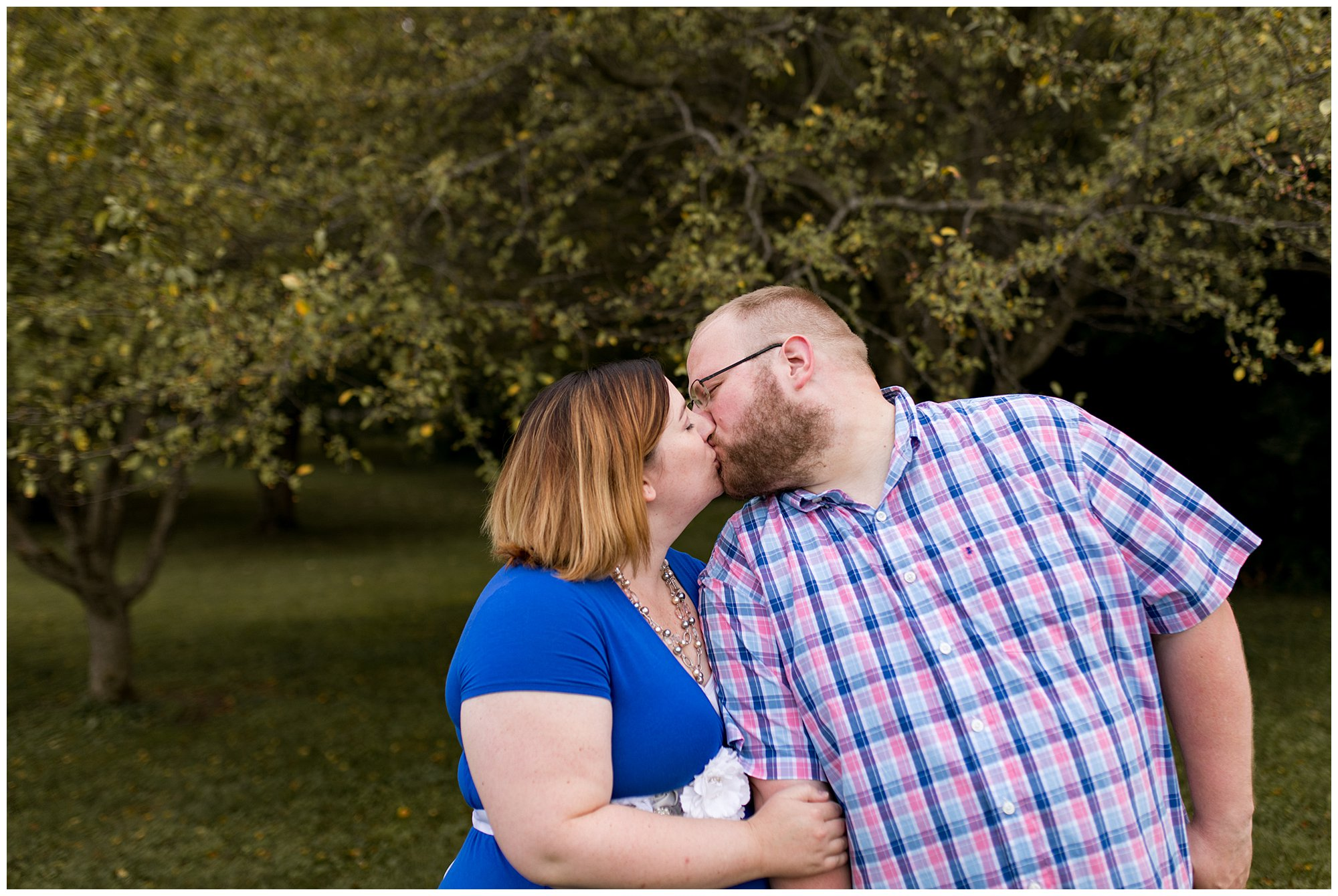 mom and dad kiss during Kokomo Indiana maternity session at Jackson Morrow Park