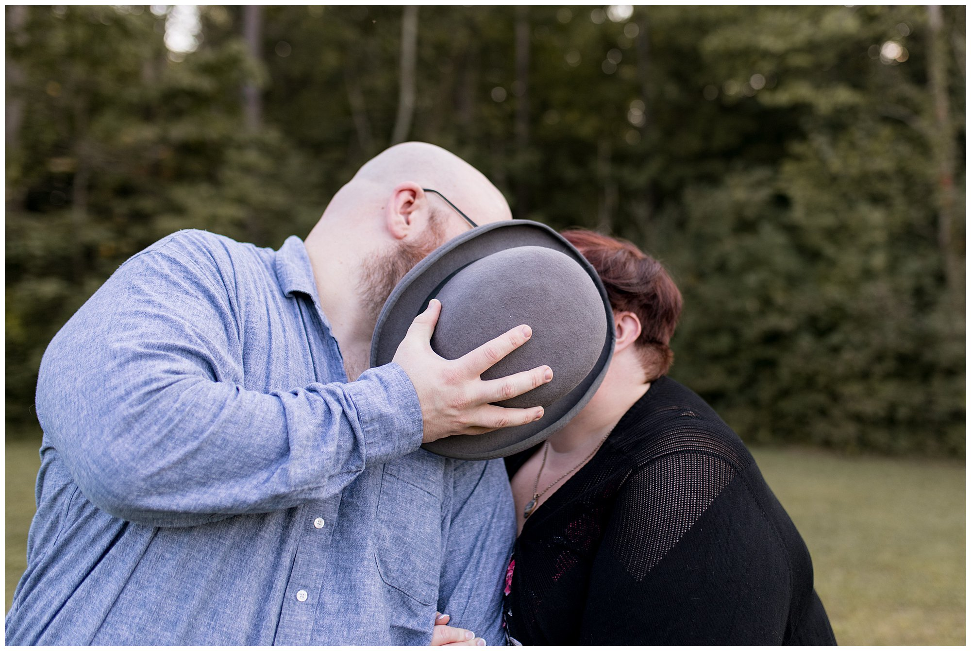 couple kisses behind hat during Indianapolis engagement session at Fort Harrison State Park