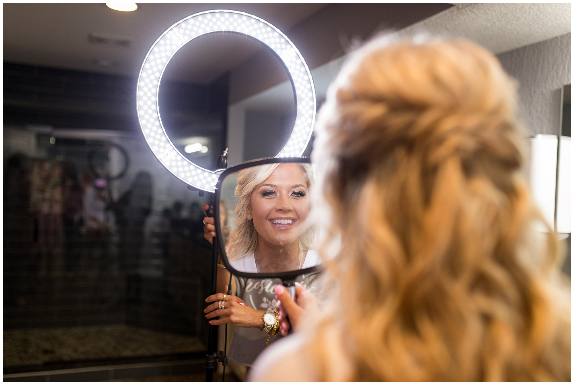 bride seeing her finished makeup for the first time on her wedding day