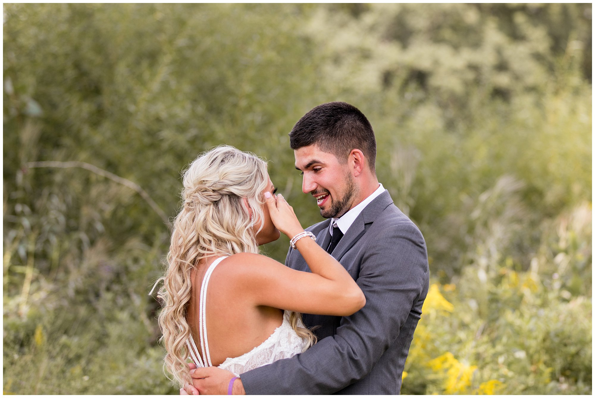 bride wipes away tears after seeing groom for first time on wedding day in Fort Wayne