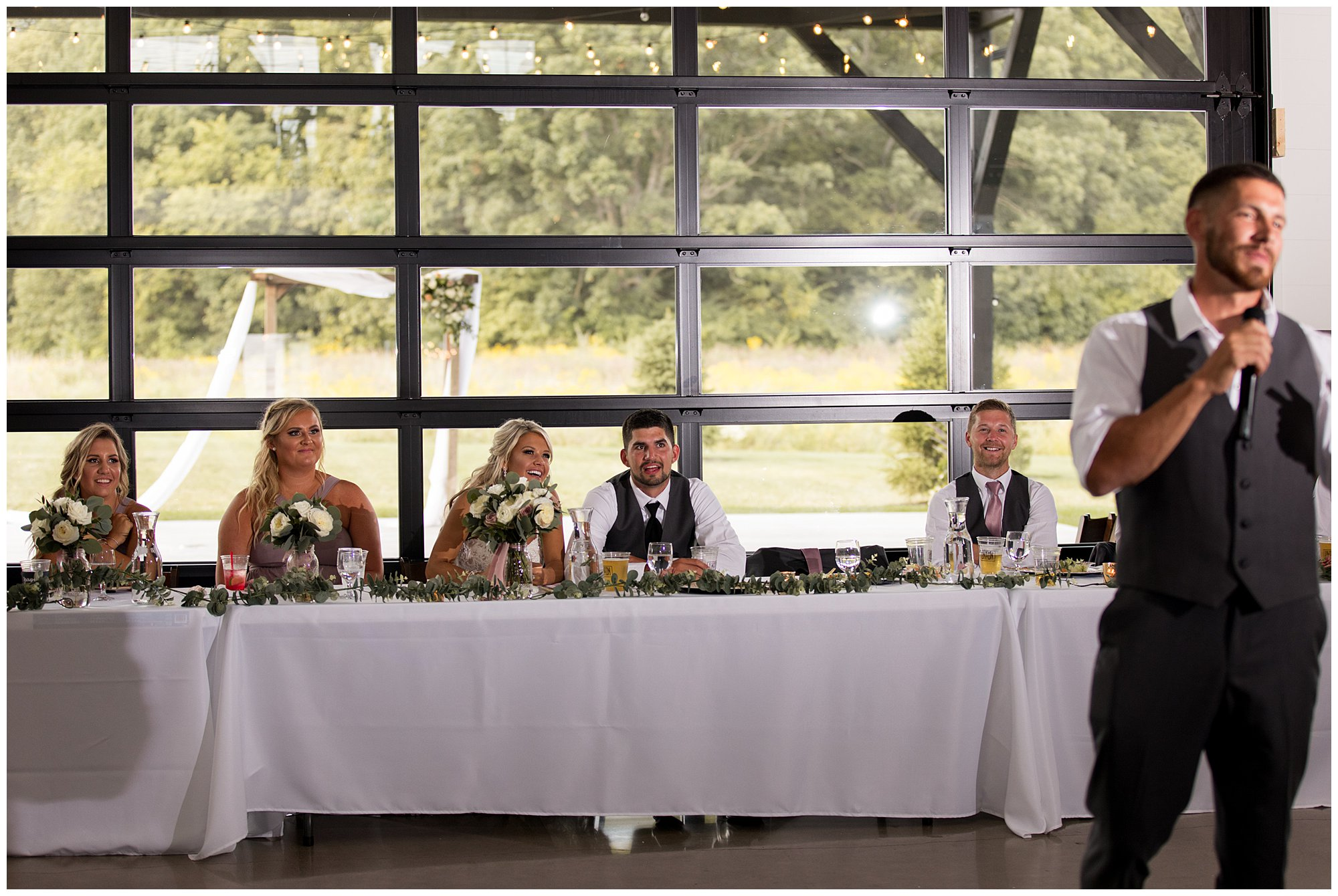 bride and groom laugh during best man's speech at Union 12 wedding reception