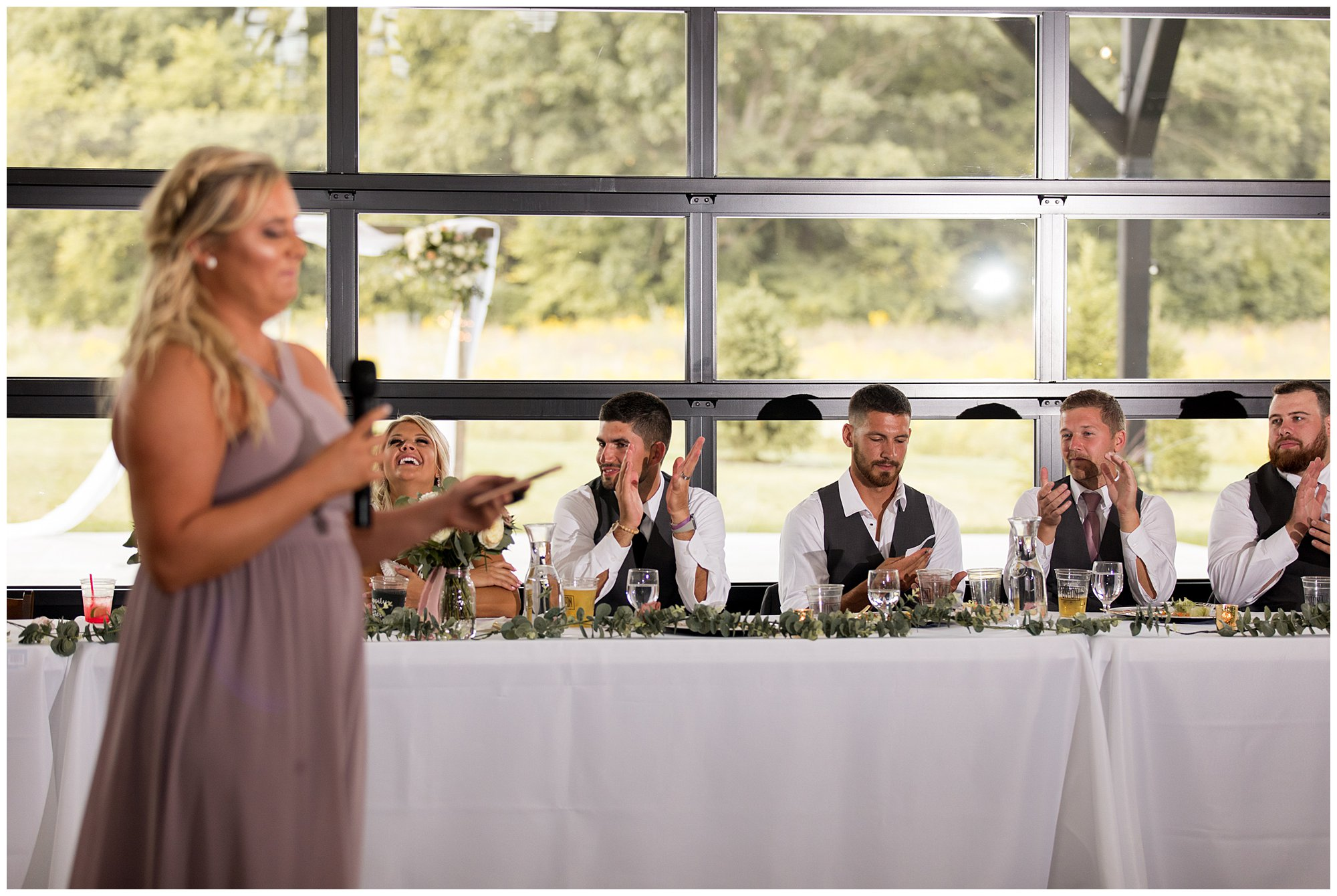 bride and groom laugh during maid of honor's speech at Union 12 wedding reception