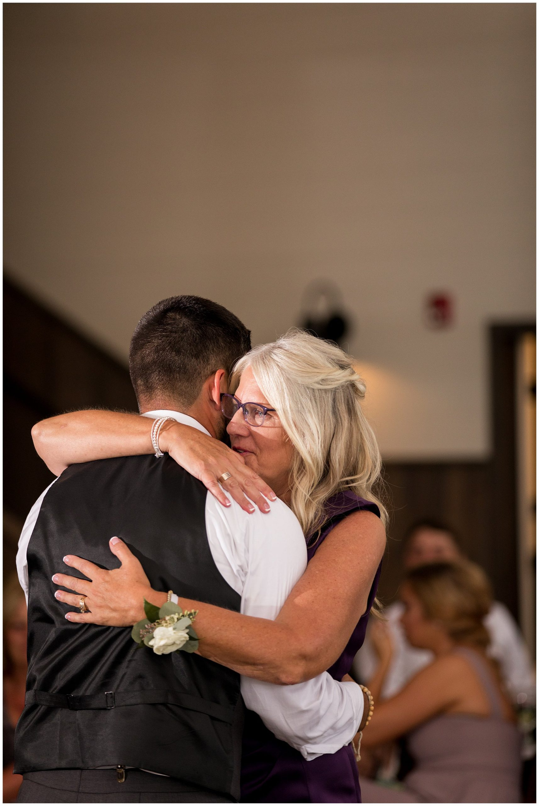 groom and mother dance together during Union 12 wedding reception in Fort Wayne