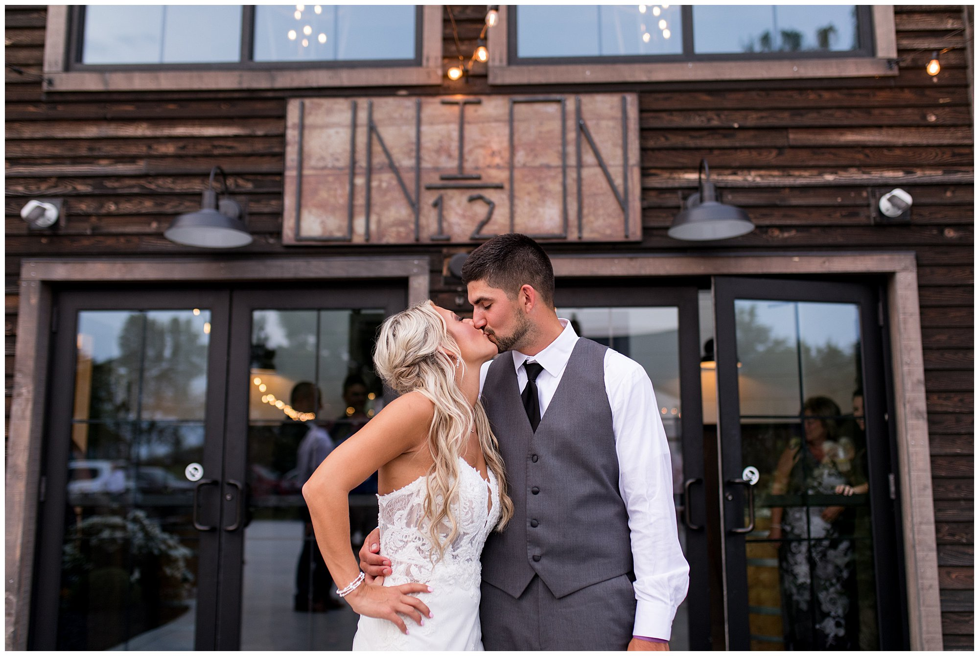 bride and groom kiss in front of Union 12 wedding venue sign in Fort Wayne