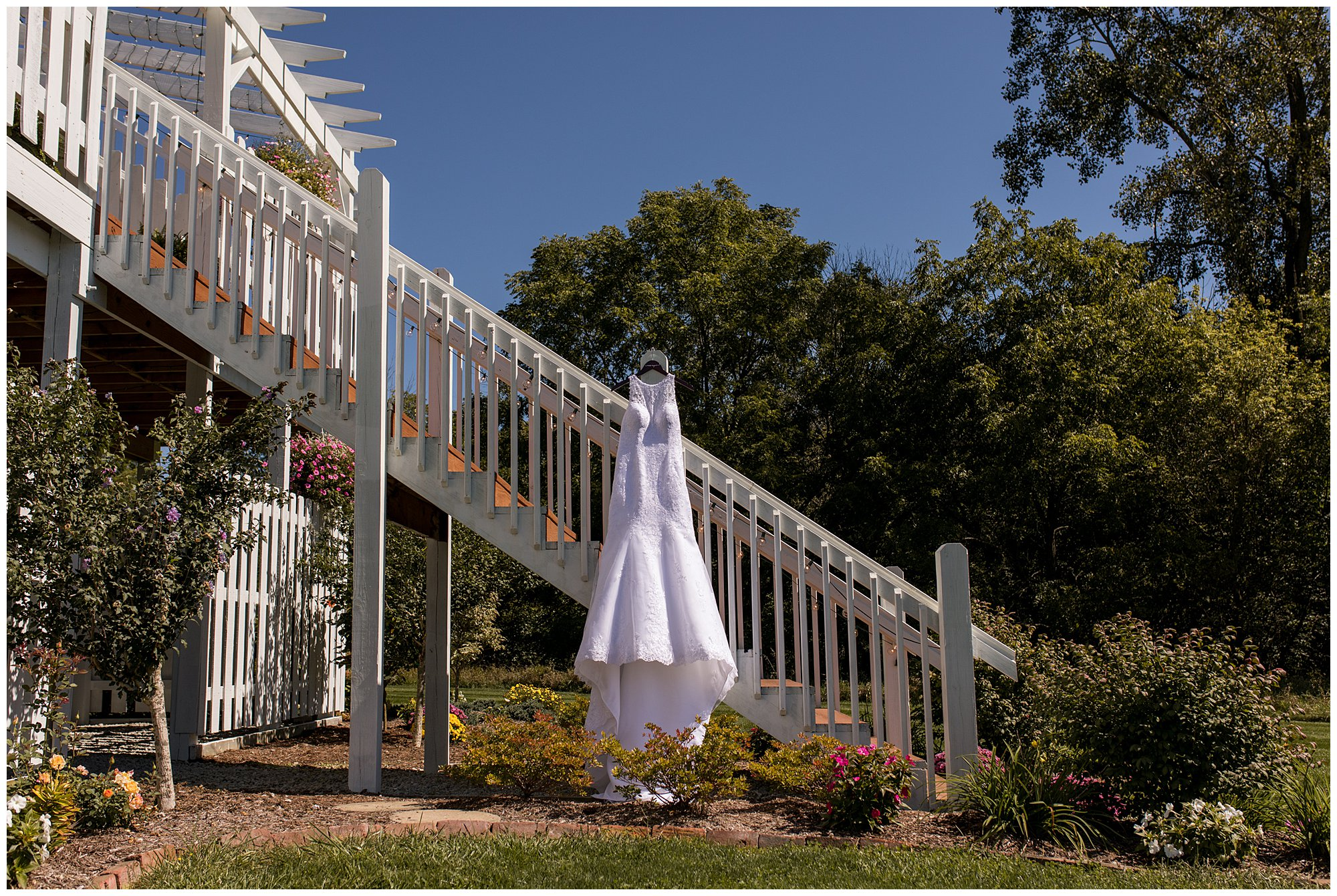 bride's wedding dress hanging from deck at Legacy Barn in Kokomo Indiana