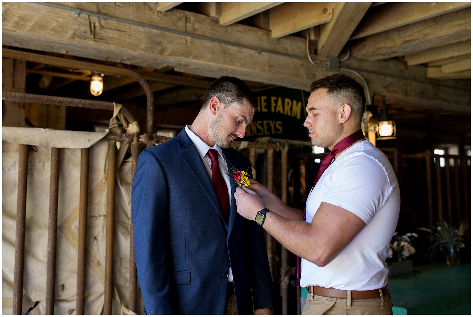 best man pinning boutonniere on groom at Legacy Barn in Kokomo