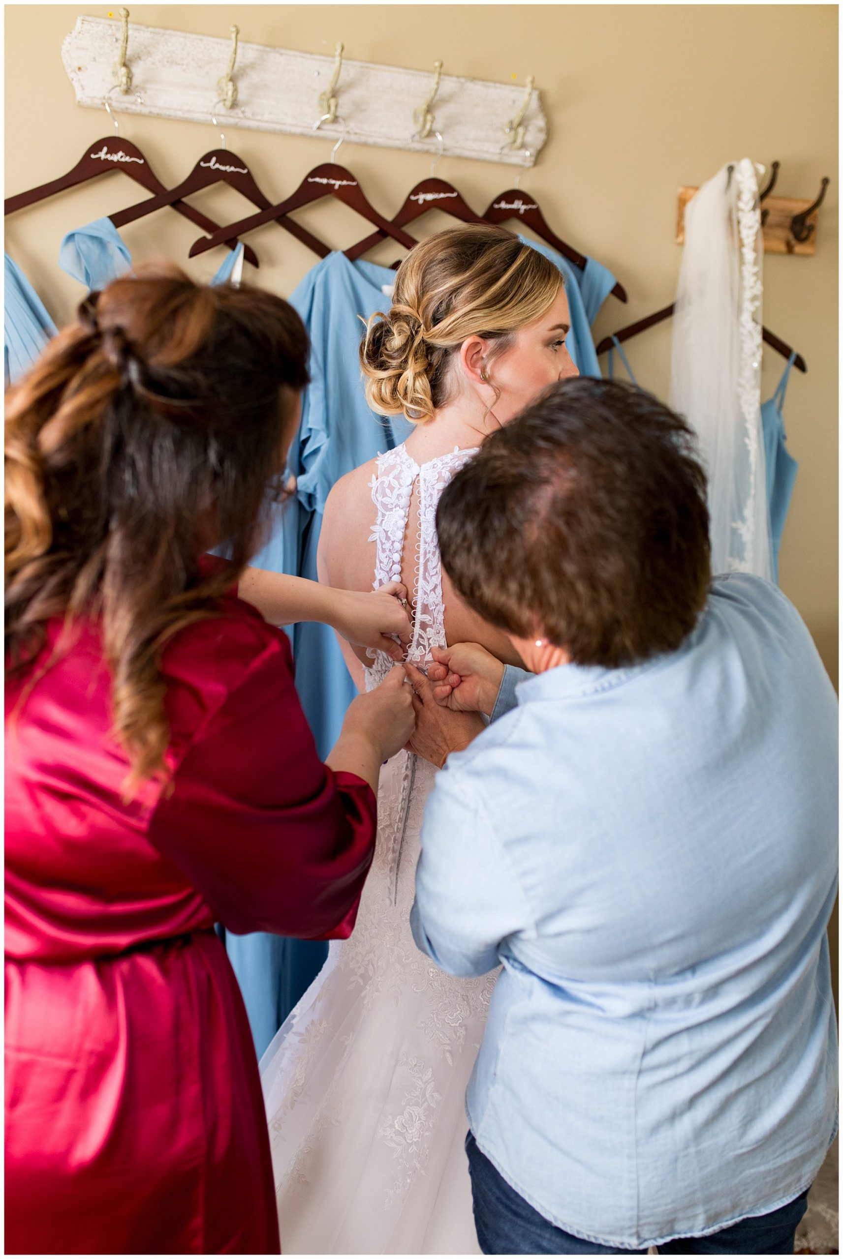 mom and sister button bride into dress before wedding at Legacy Barn