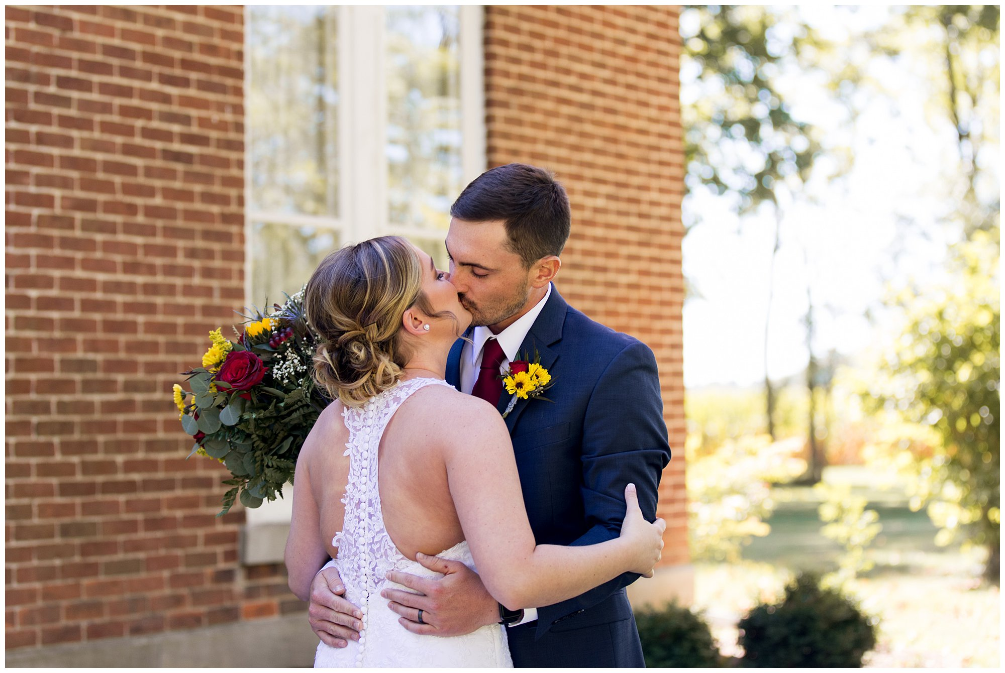 bride and groom kiss after first look at Legacy Barn wedding venue in Kokomo Indiana