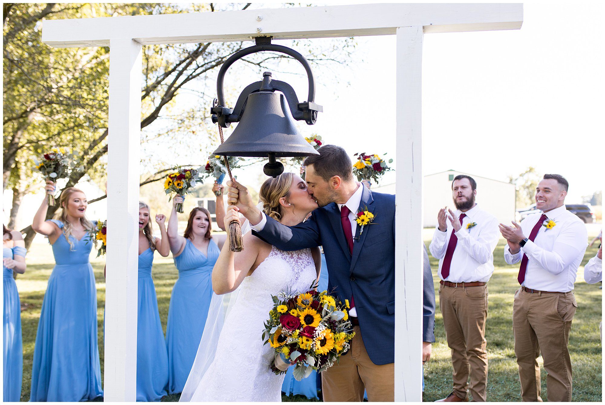 bride and groom kiss and ring the legacy bell at Kokomo's Legacy Barn wedding venue