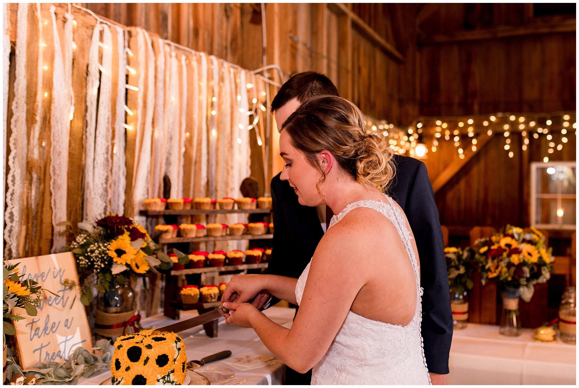 bride and groom cut cake together at Legacy Barn wedding reception in Kokomo