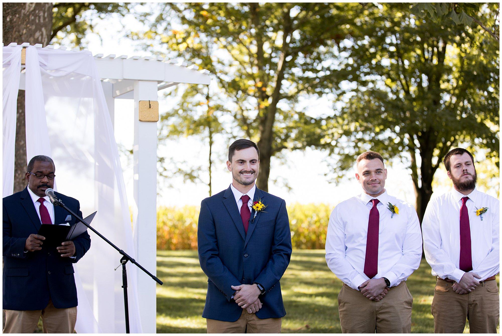 groom smiles as bride comes down wedding aisle at Legacy Barn in Kokomo