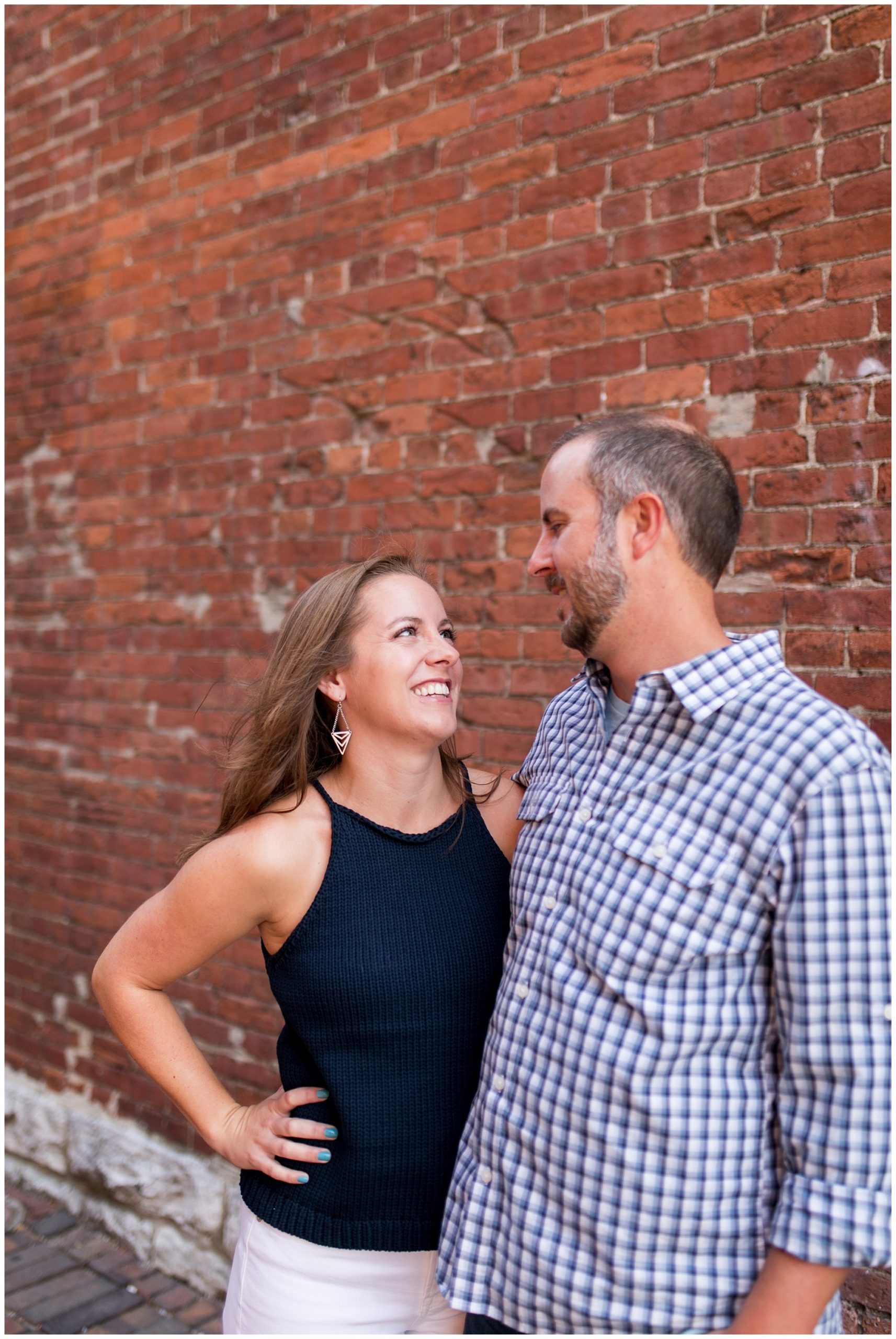 couple smiles at each other during engagement photos at Mass Ave in Indianapolis