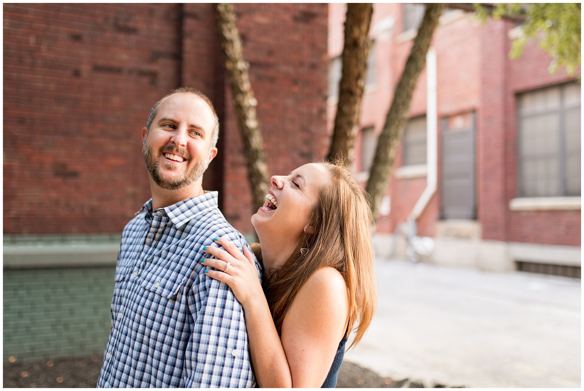 bride and groom laugh together during casual Indianapolis engagement session at Mass Ave