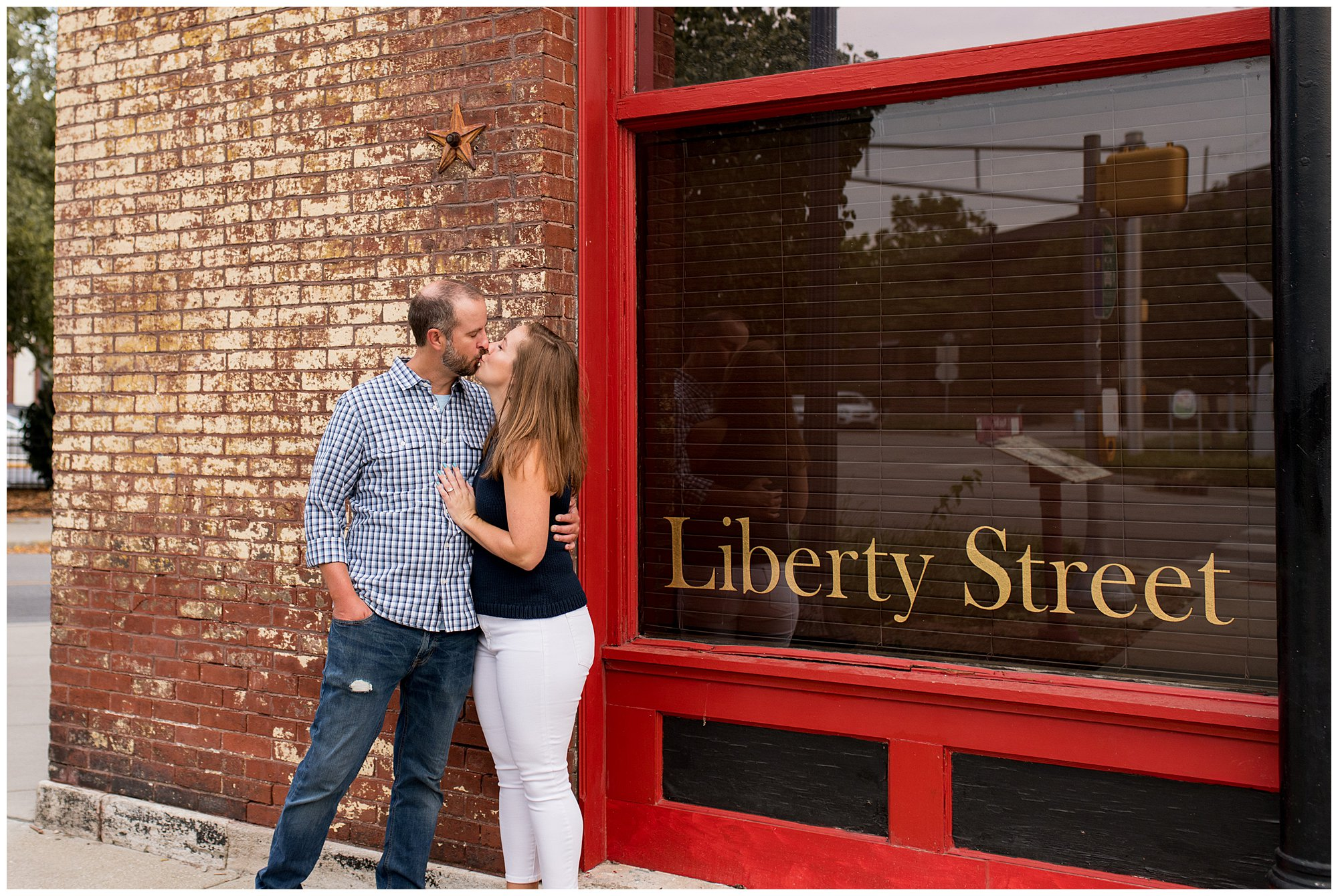 bride and groom kiss in front of bar during Indianapolis engagement session