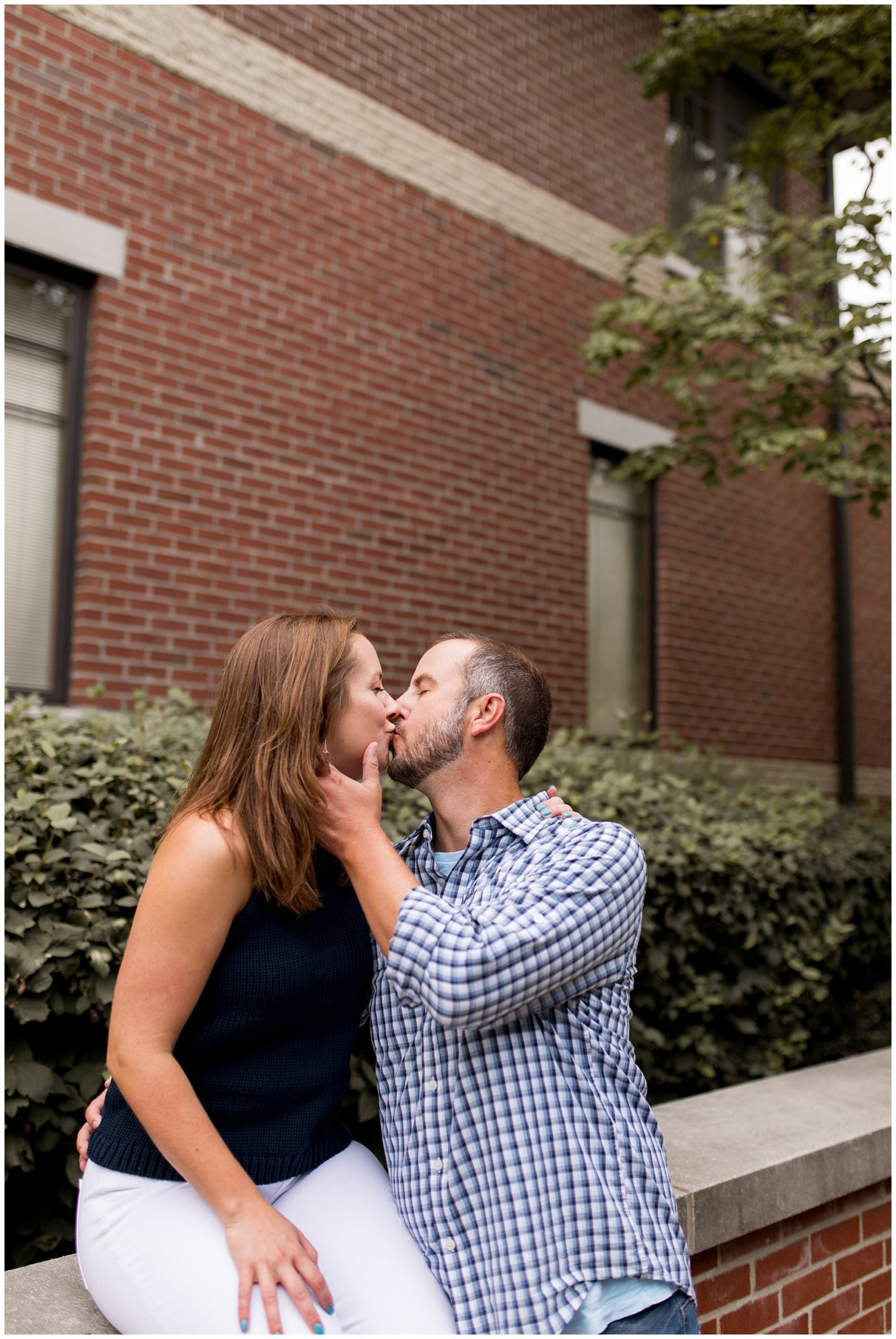 bride and groom kiss along Mass Ave during Indianapolis engagement session