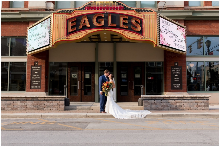 bride and groom in front of Eagles Theatre sign in downtown Wabash