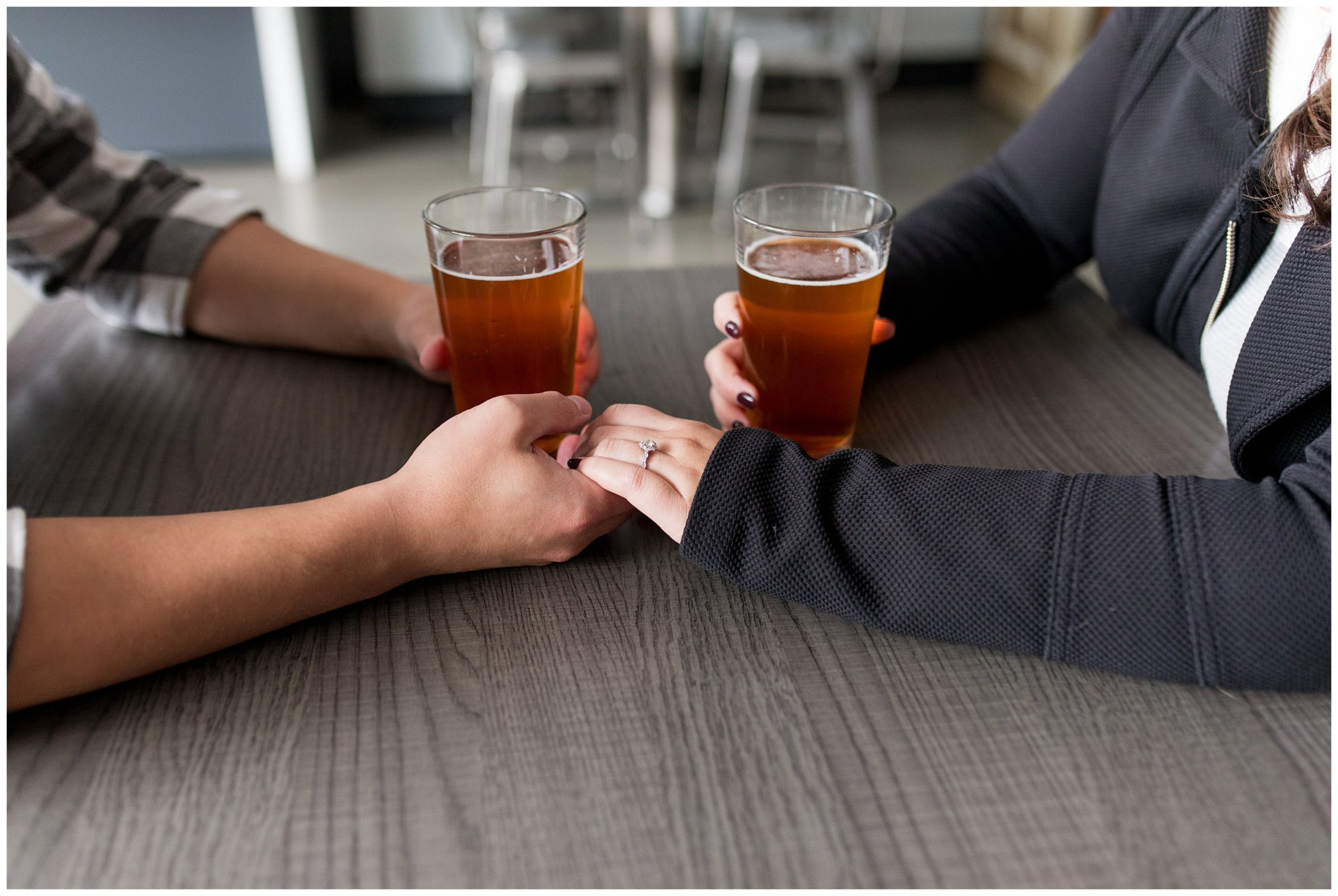 couple holding hands over beers at Tappers Arcade Bar in Indianapolis