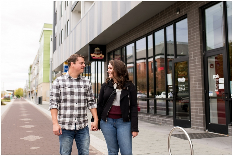 couple holding hands during engagement session outside of Tappers Arcade Bar in Indianapolis