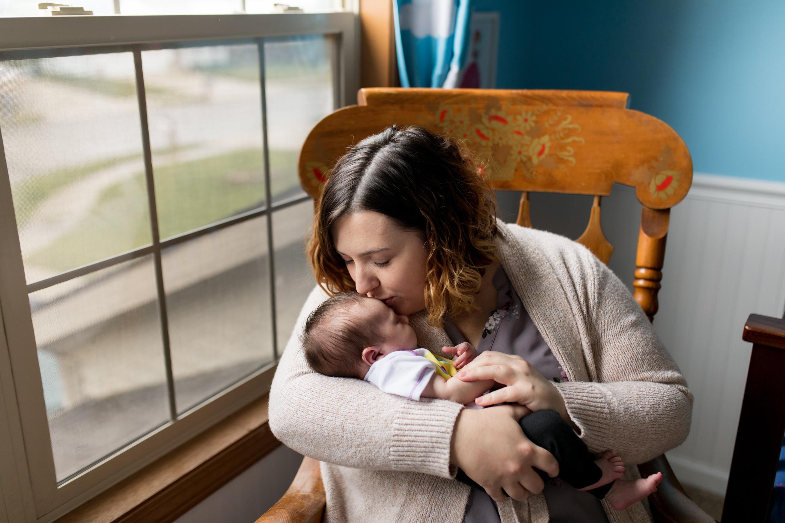 mom kisses newborn baby in Toy Story nursery theme