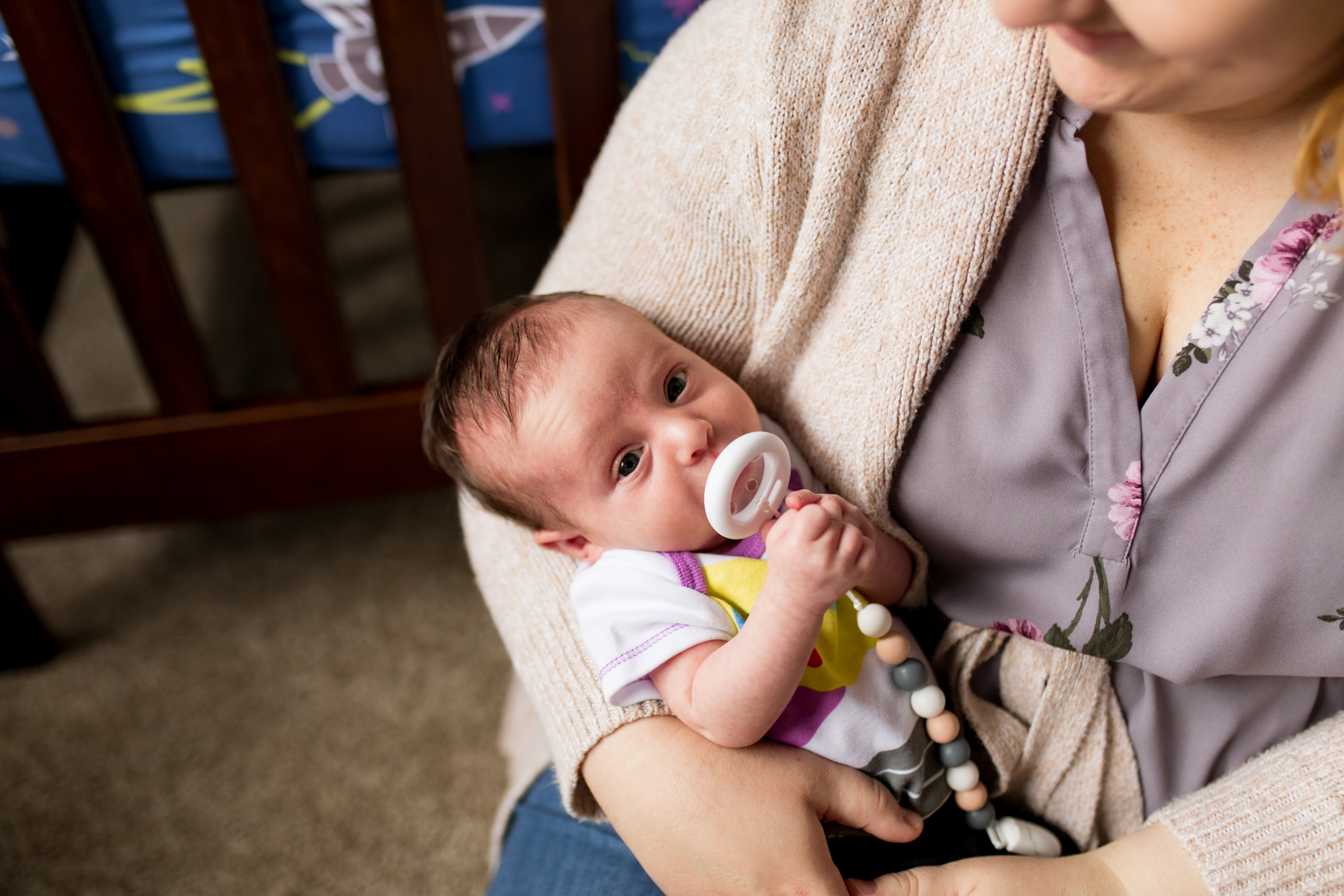 mom and dad hold newborn baby in Toy Story-themed nursery