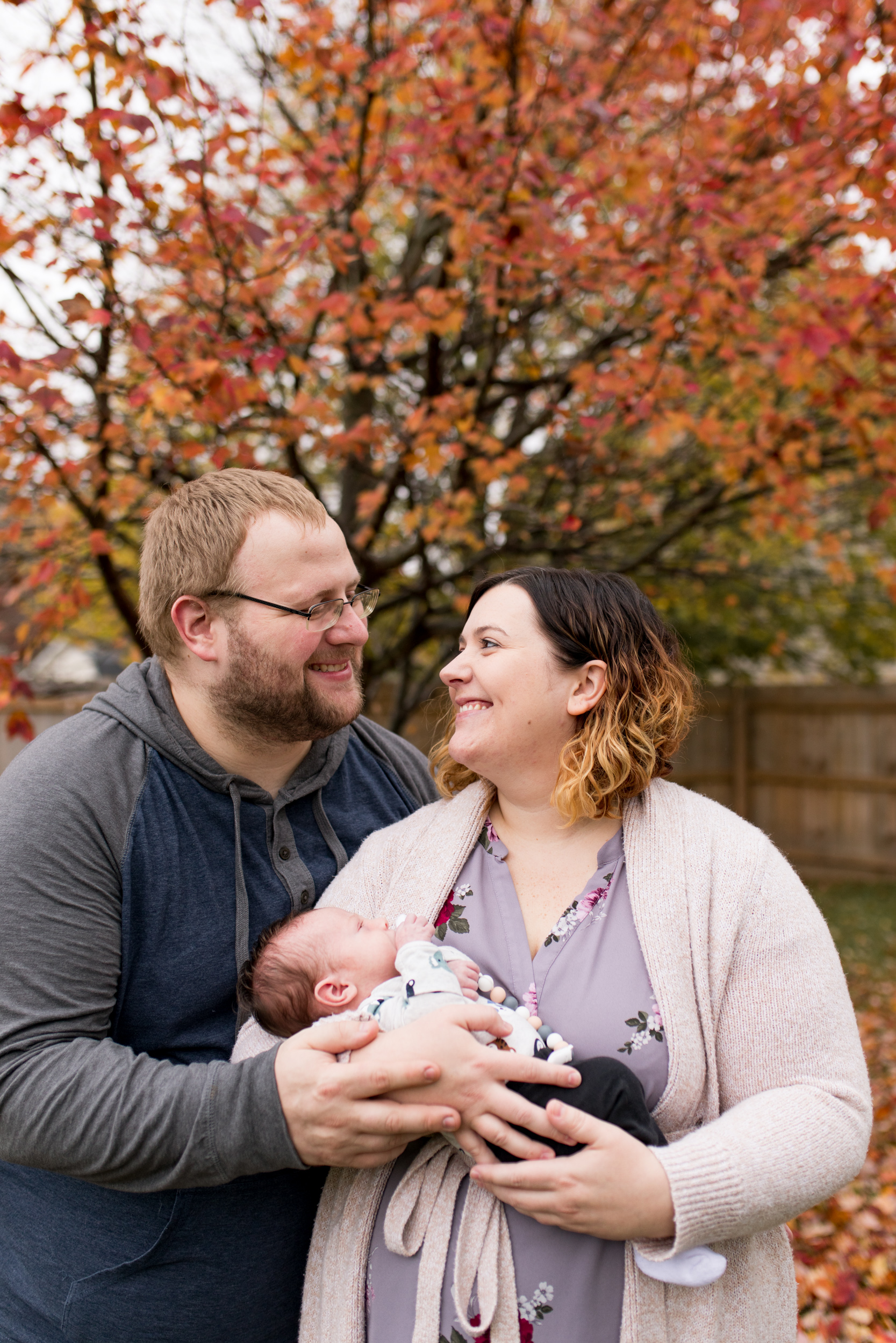 mom and dad hold newborn baby outside of home