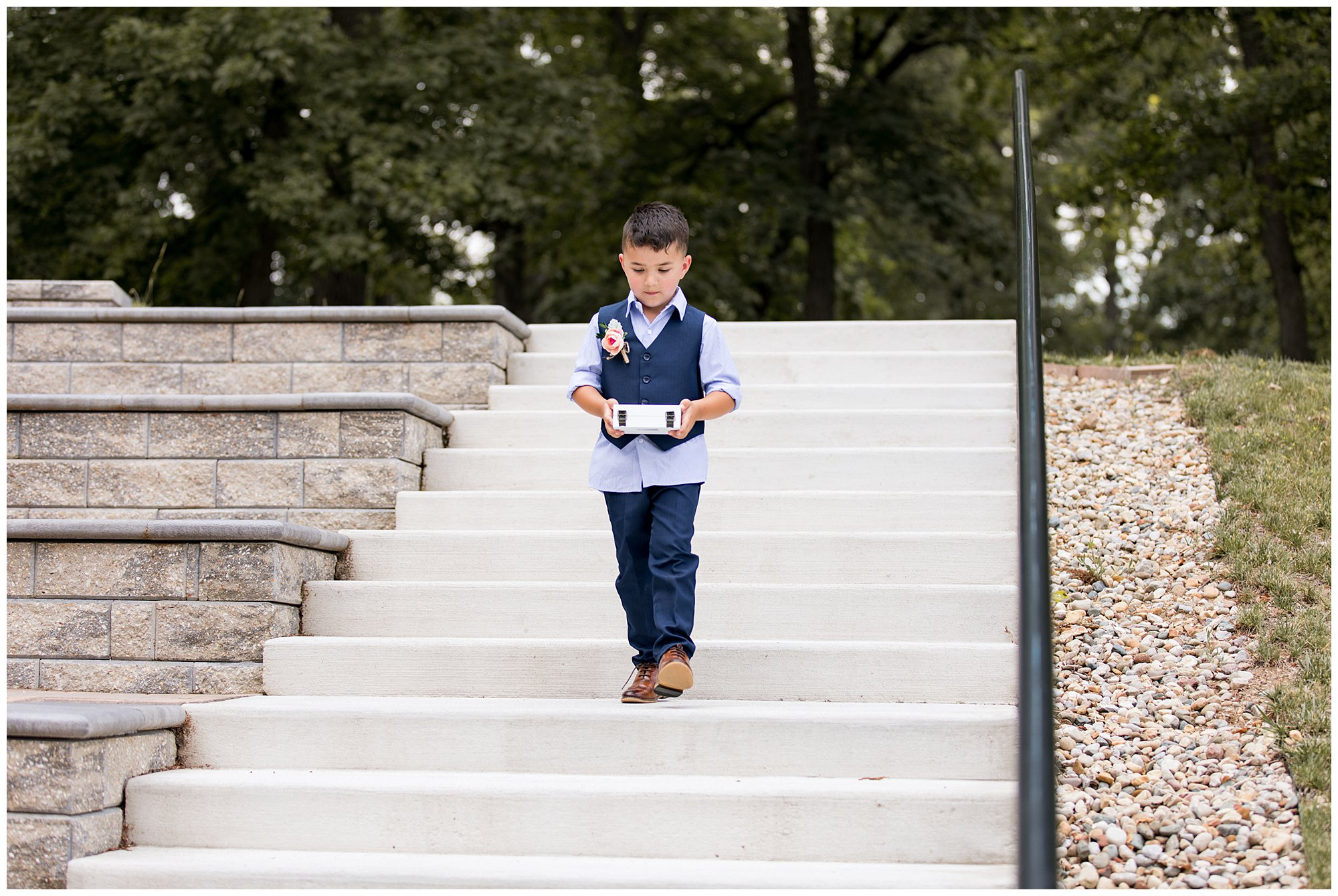 ring bearer brings rings down the stairs at Lucerne Park amphitheatre