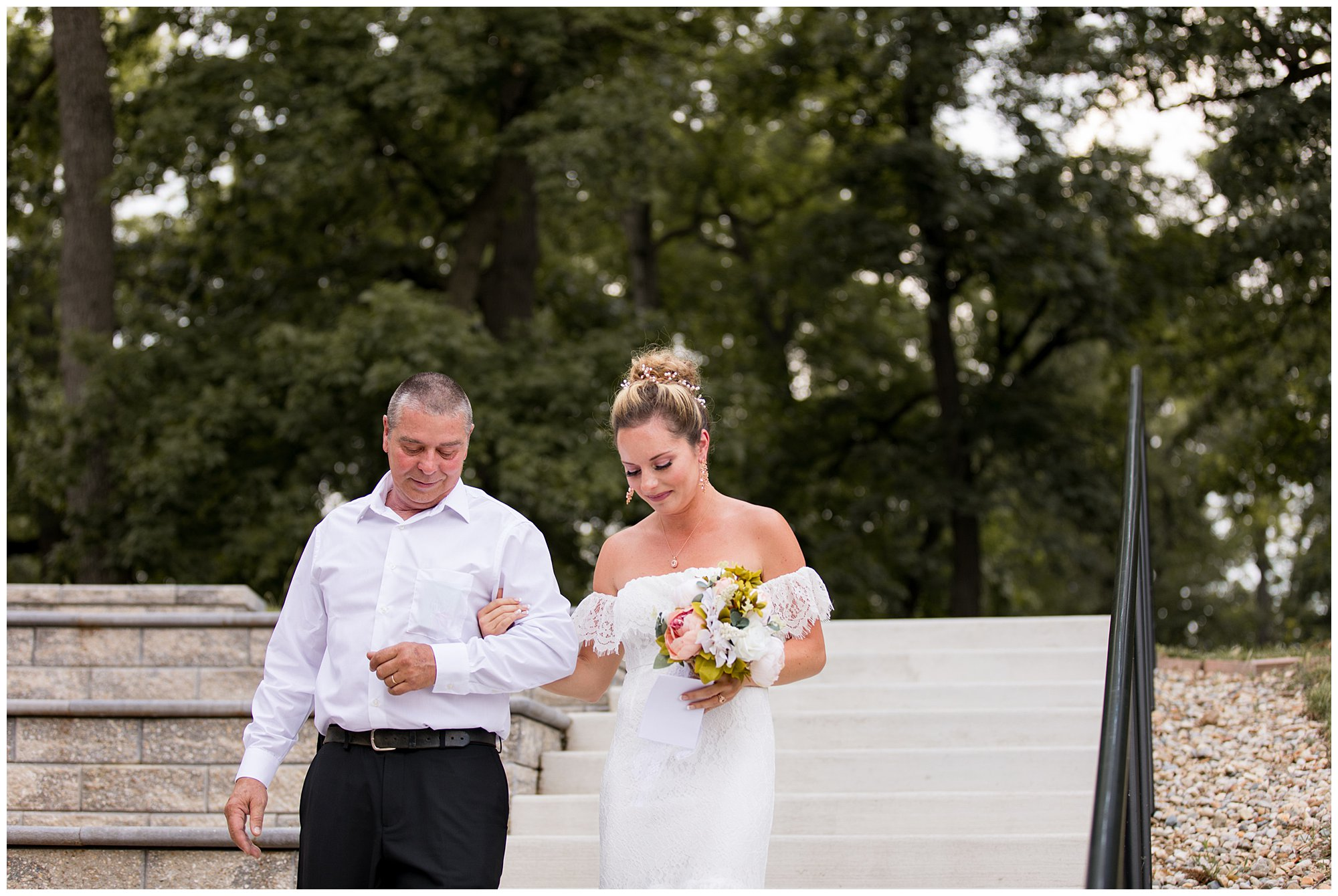 bride walks down steps with father during wedding ceremony in Warsaw Indiana