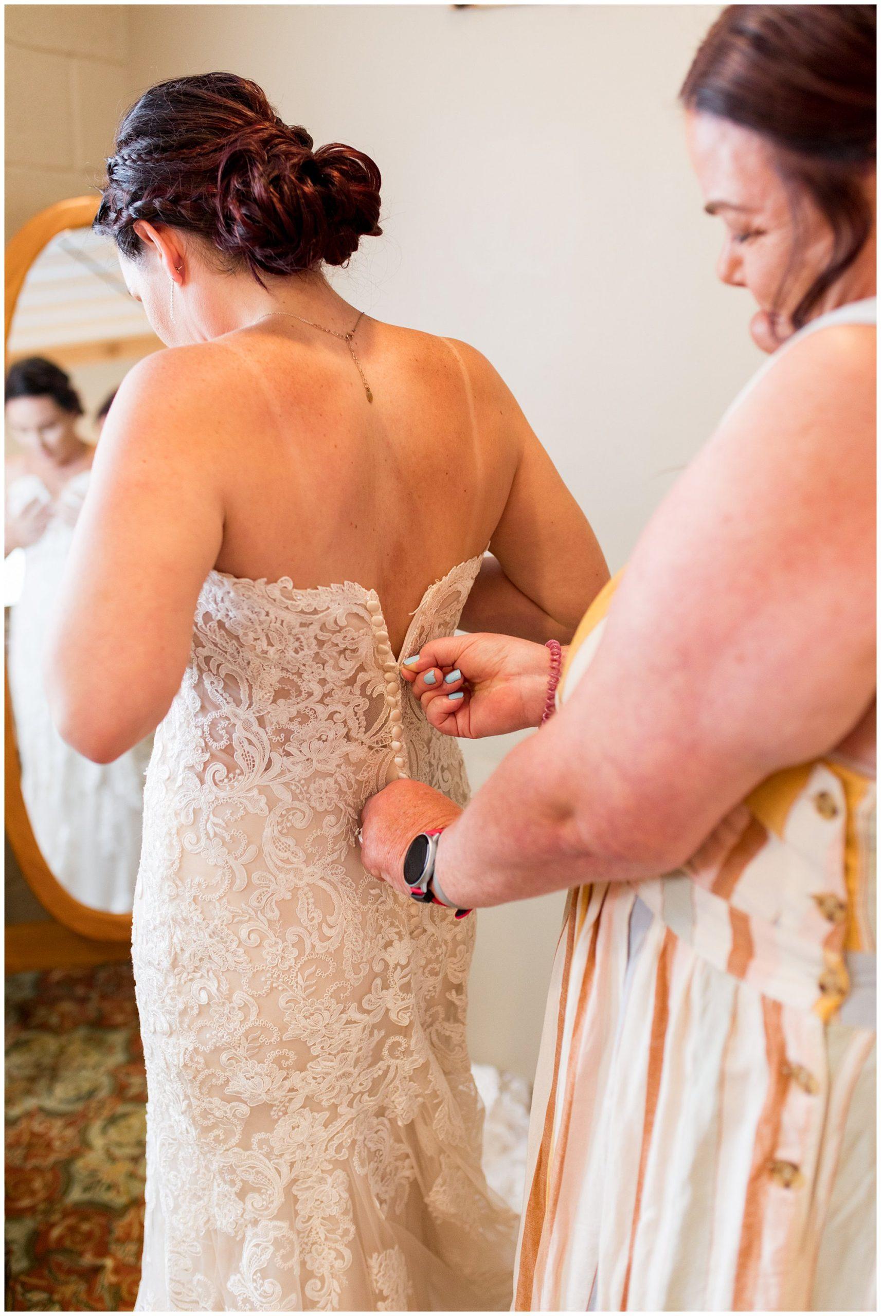 bride's mom zips her into dress from Blye's Bridal Loft in Kokomo